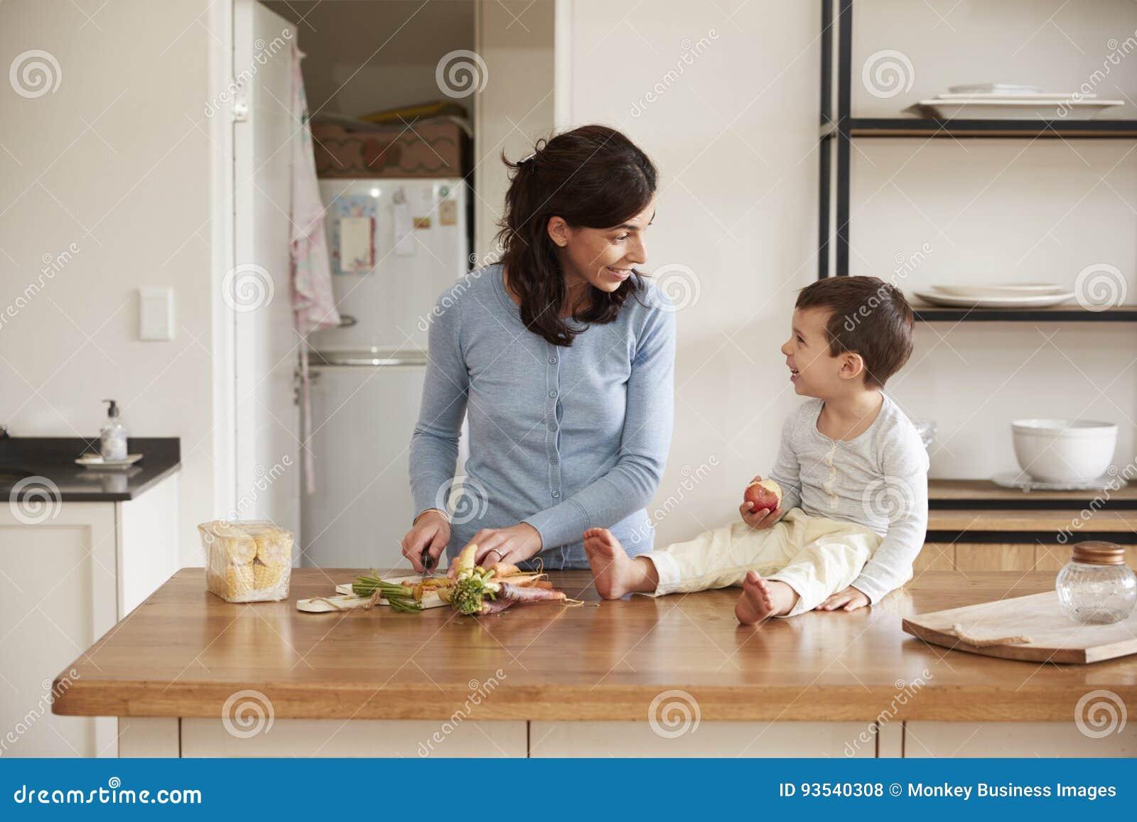 Zoon die Moeder helpen om Voedsel op Keukeneiland voor te bereiden