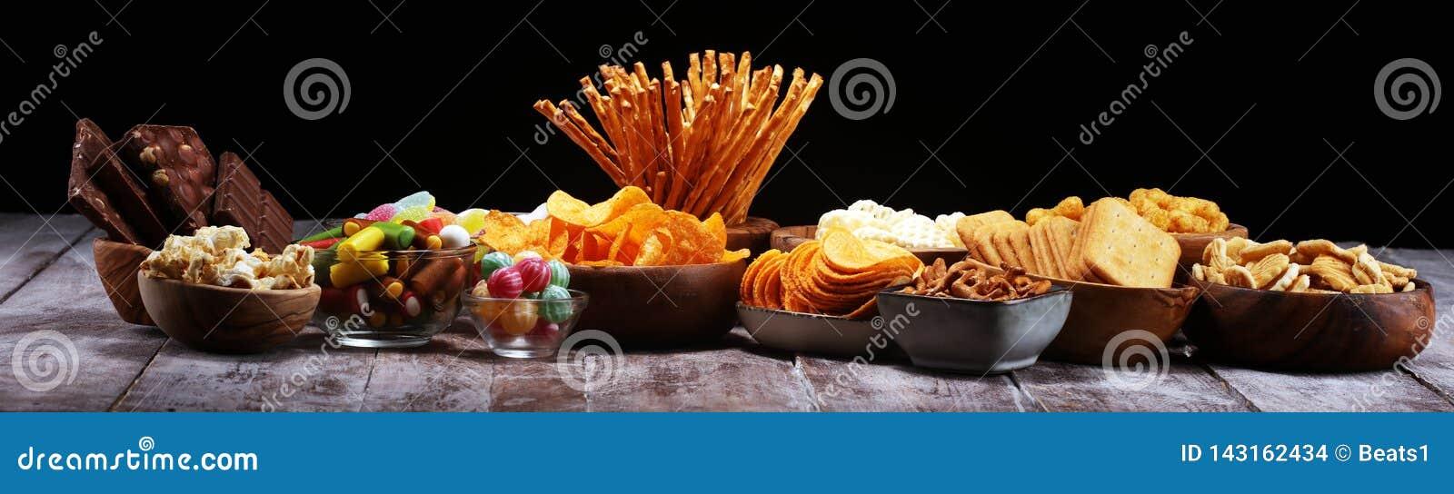 Zoute snacks Pretzels, spaanders, crackers in houten kommen op lijst