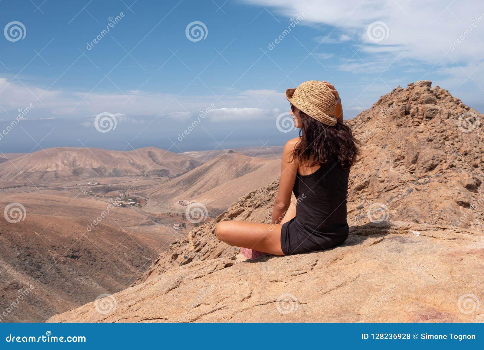Zrelaksowana dziewczyna patrzeje krajobraz z wierzchu góry