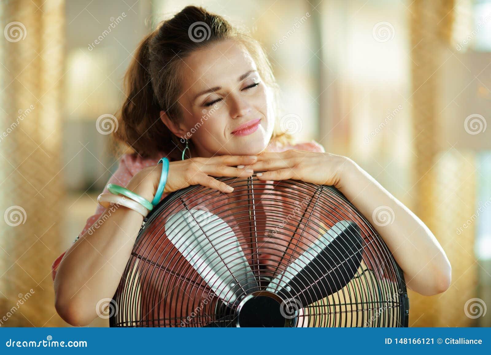 Zrelaksowana elegancka kobieta obejmuje kruszcowego podłogowego pozycji fan