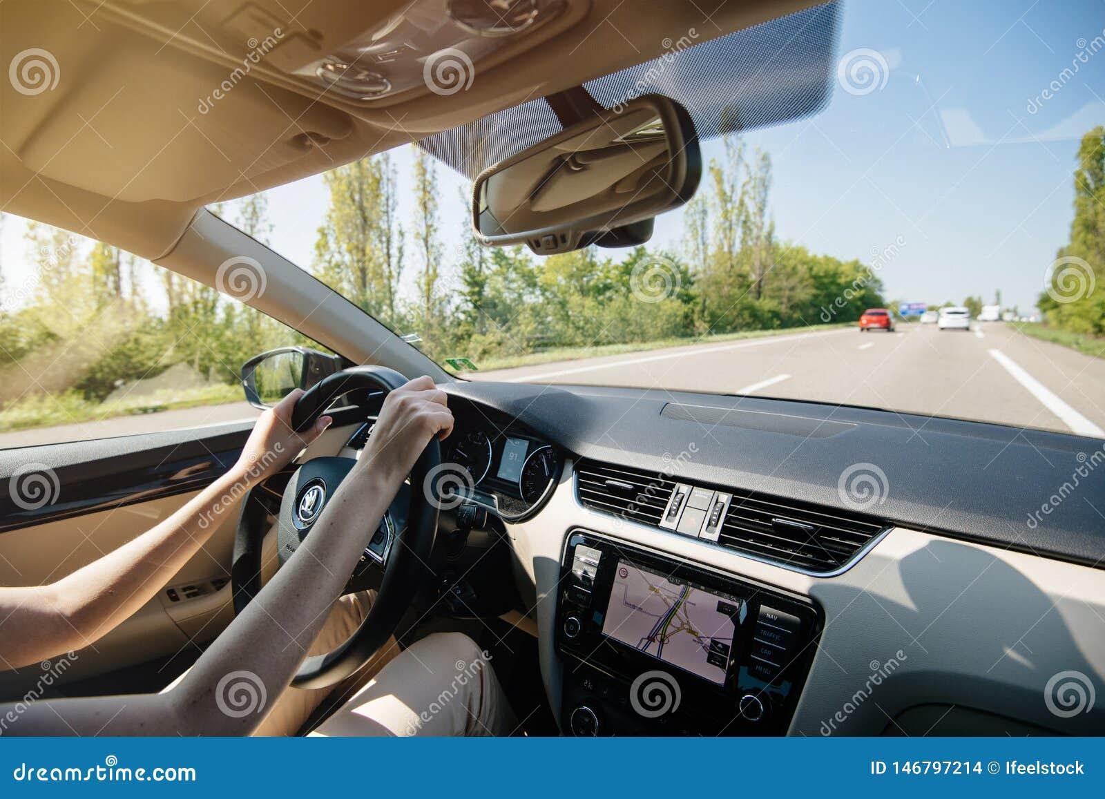 Zrelaksowana kobieta jedzie Skoda luksusowego samochód obracał dalej GPS