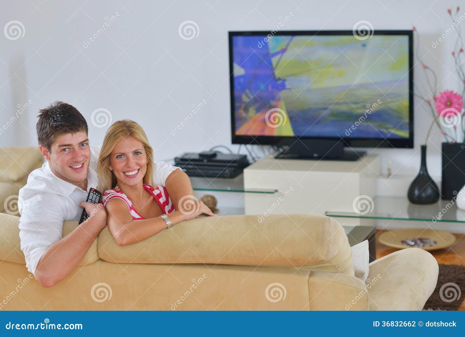 Zrelaksowana potomstwo para ogląda tv w domu