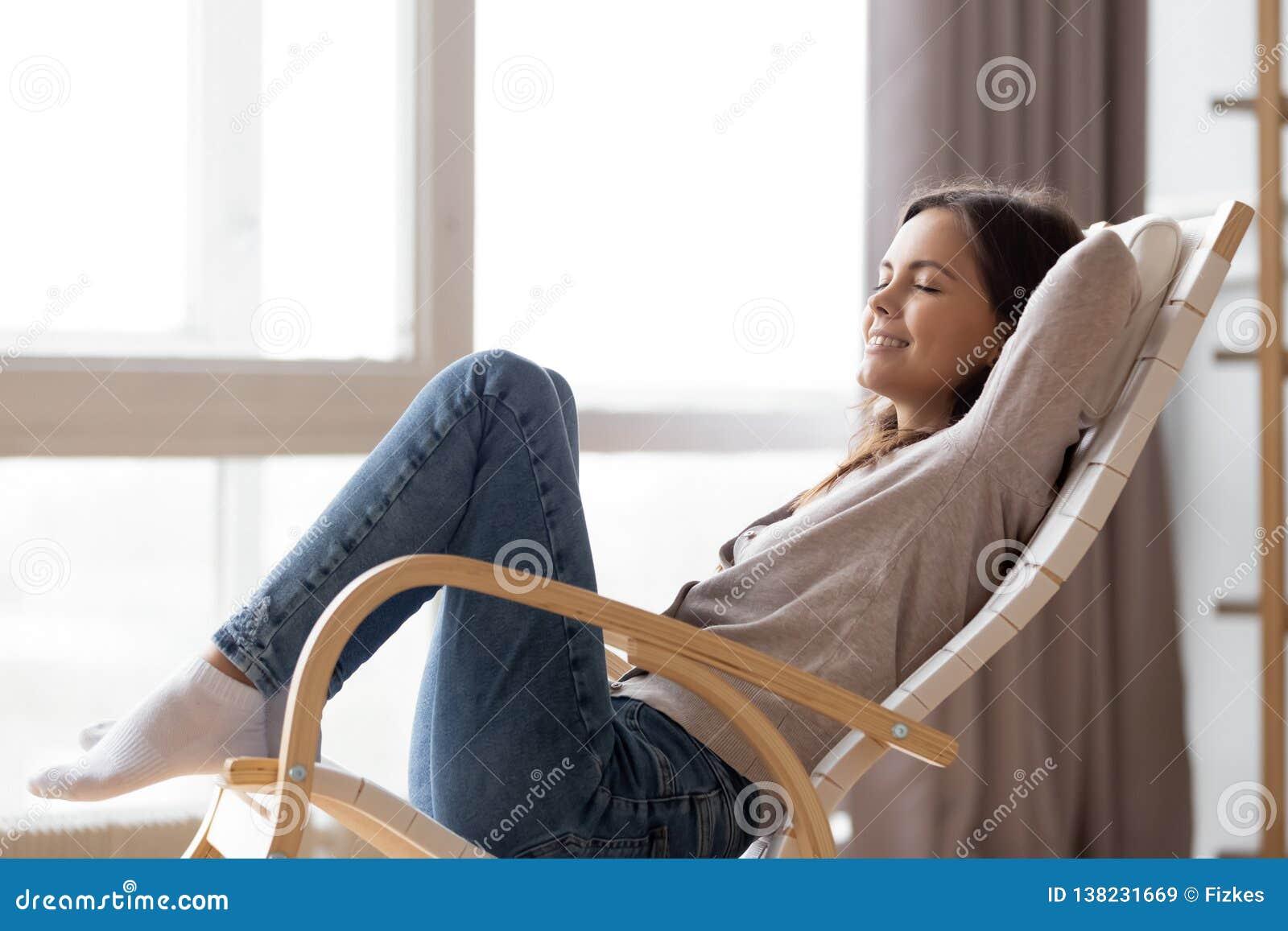 Zrelaksowanej spokojnej młodej kobiety lounging siedzieć w wygodnym kołysa krześle