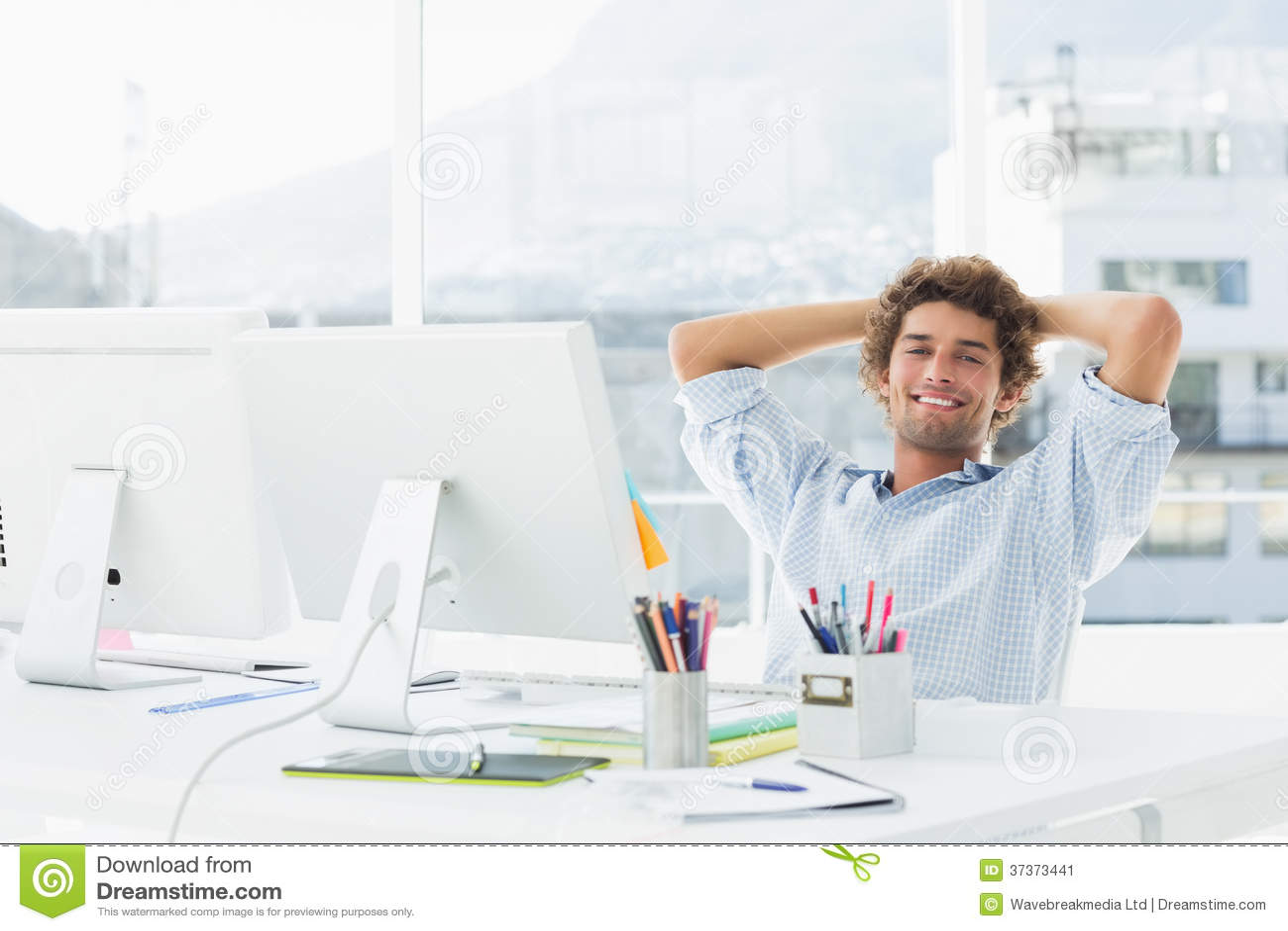 Zrelaksowany przypadkowy biznesowy mężczyzna z komputerem w jaskrawym biurze
