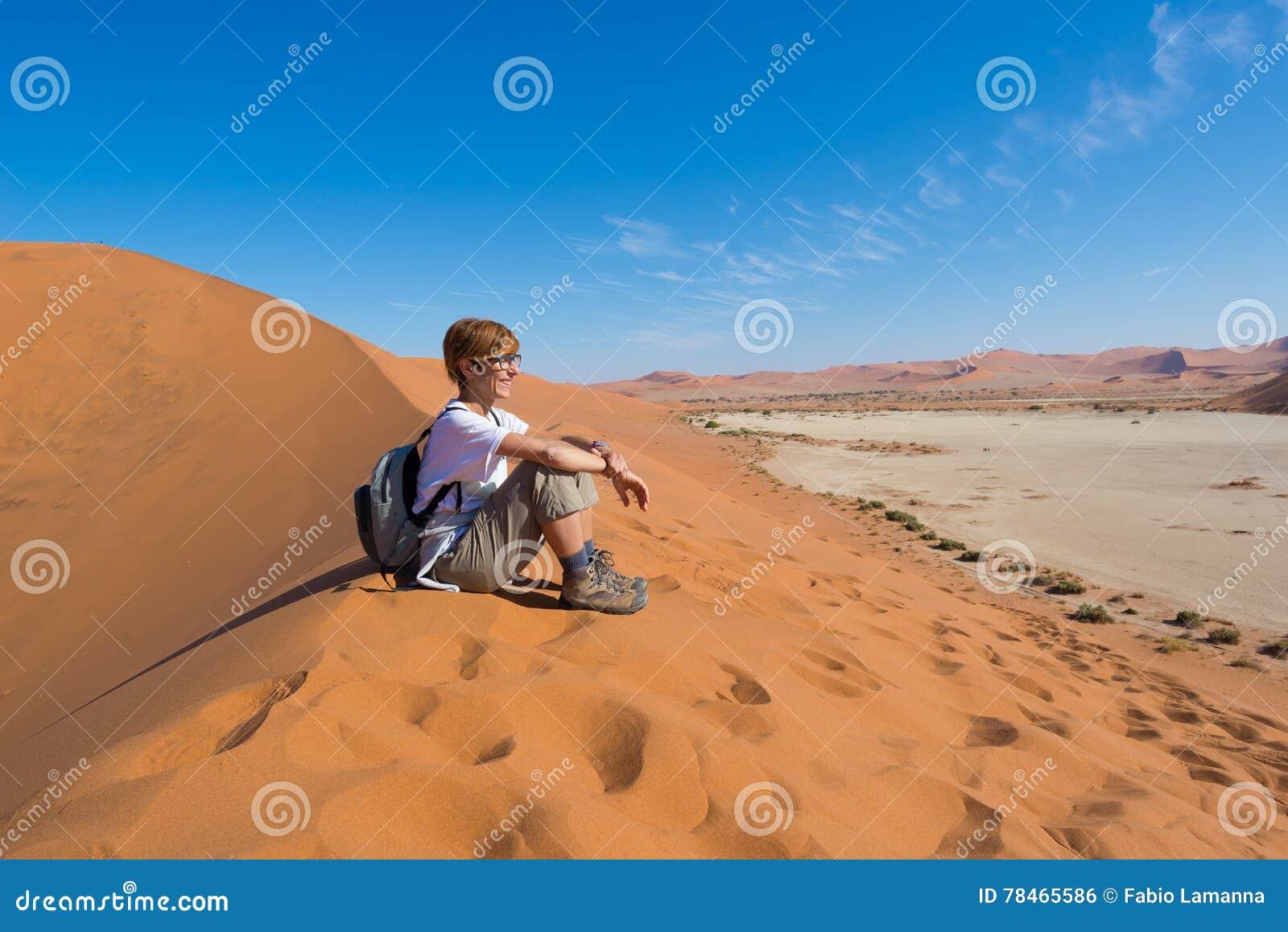 Zrelaksowany turystyczny obsiadanie na piasek diunach i patrzeć oszałamiająco widok w Sossusvlei, Namib pustynia, najlepszy podró