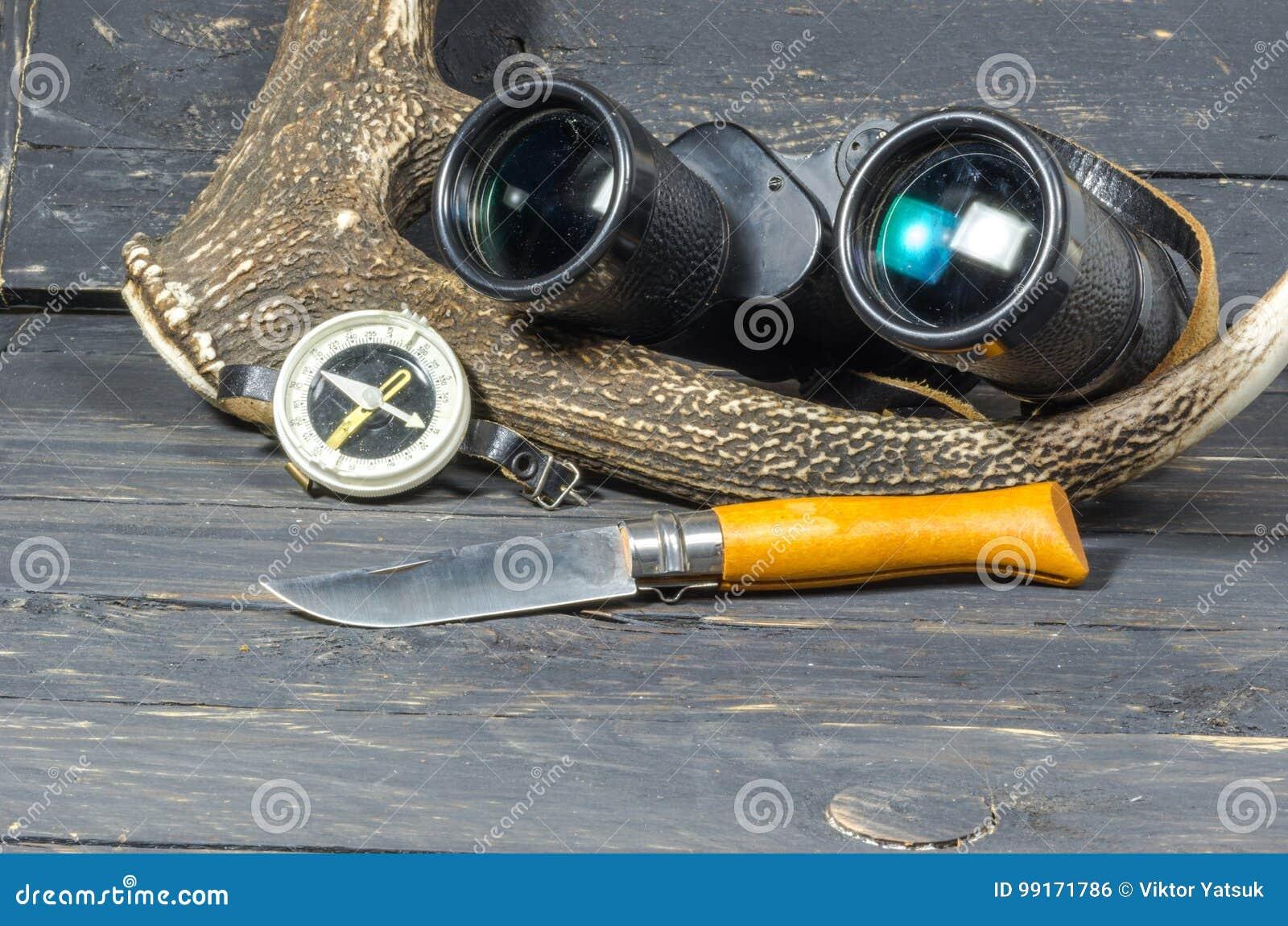Zubehör für die jagd ferngläser ein messer und ein kompass liegen