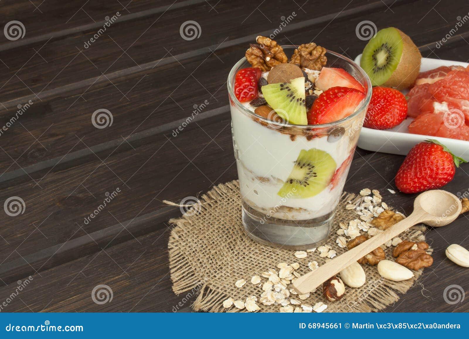 Zubereitung des gesunden Frühstücks für Kinder Jogurt mit Hafermehl, Frucht, Nüssen und Schokolade Hafermehl zum das Frühstück, d