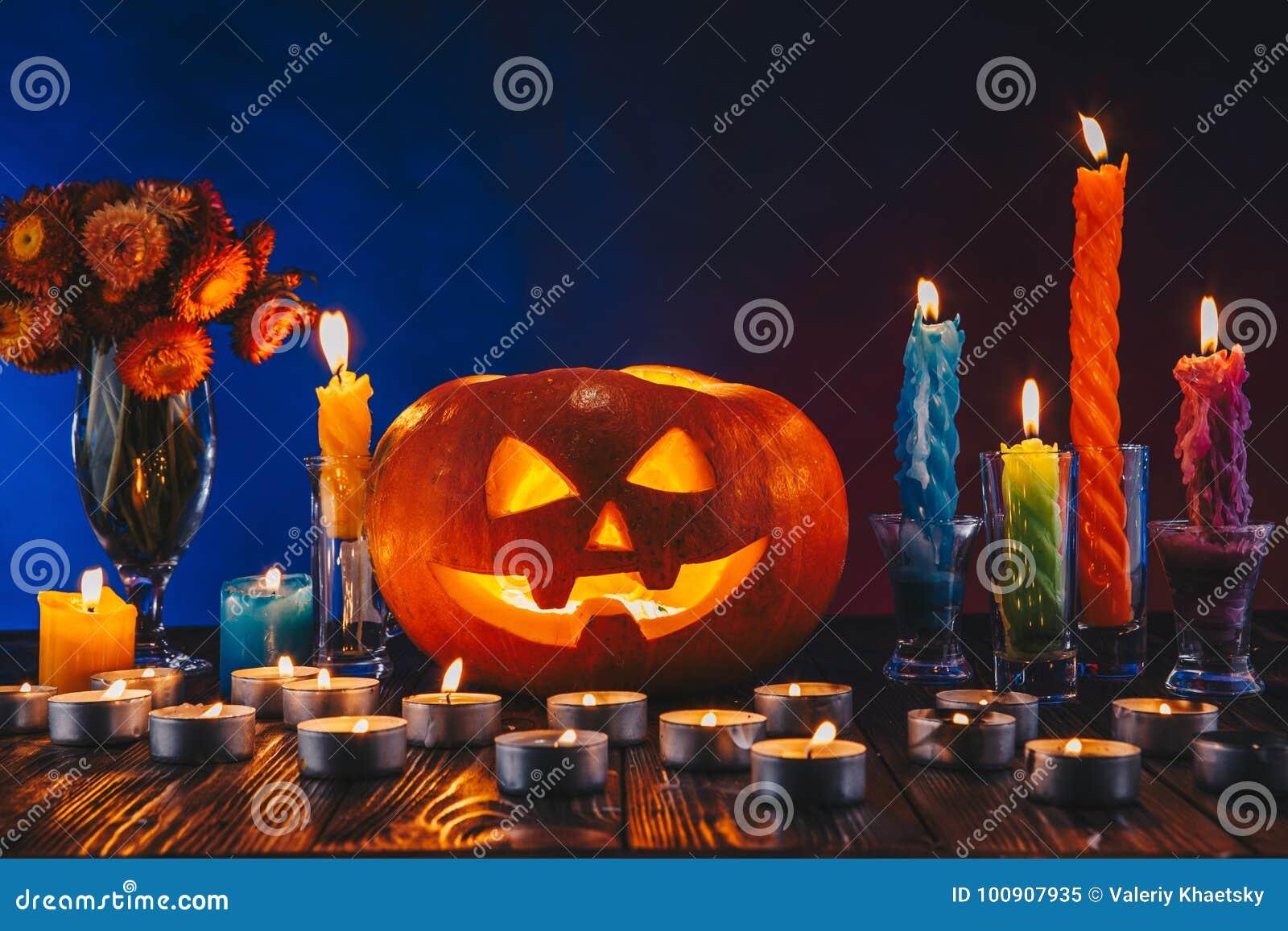 Zucca di halloween con molti candele e fiori nell illuminazione