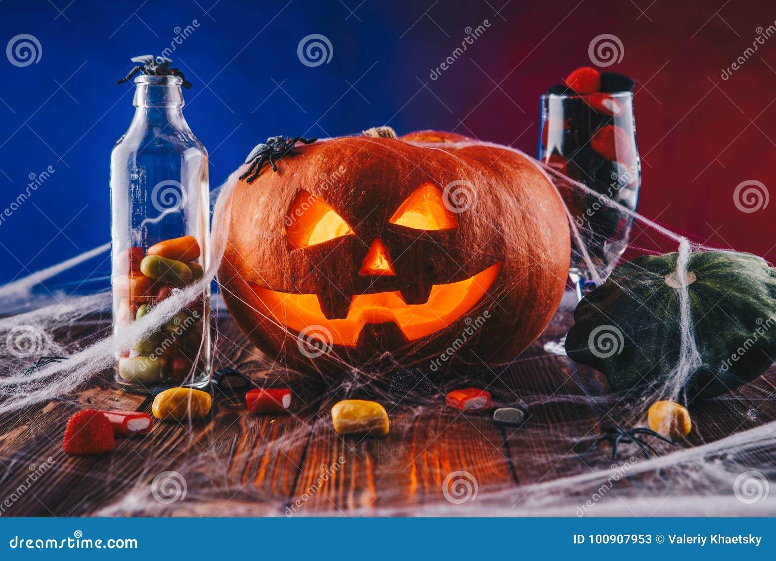 Zucca di halloween in ragnatela con i dolci e l illuminazione