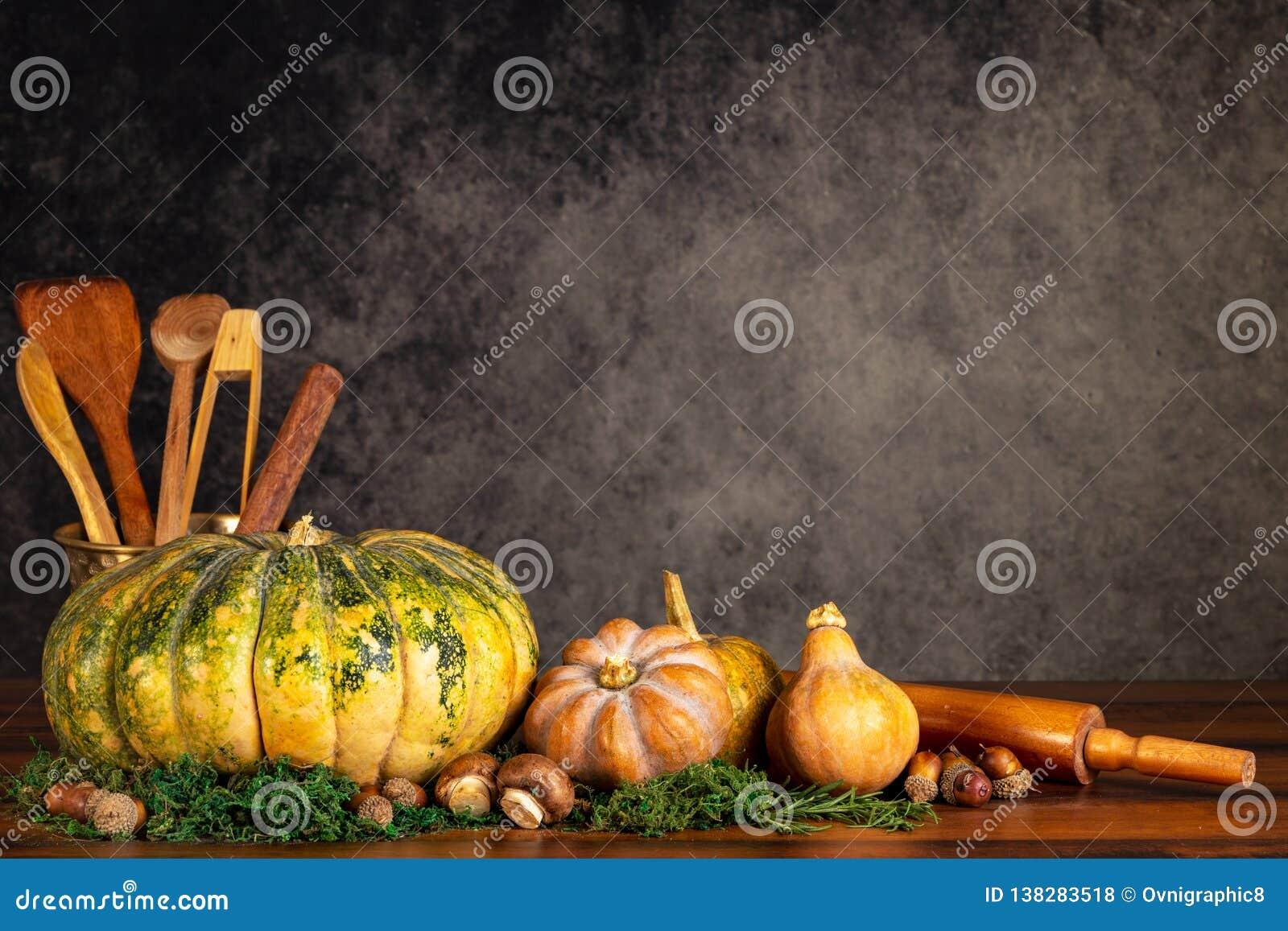 Zucche, noci di burro e funghi con la cottura i ustencils e del matterello su una tavola sopra un fondo d annata con lo spazio de