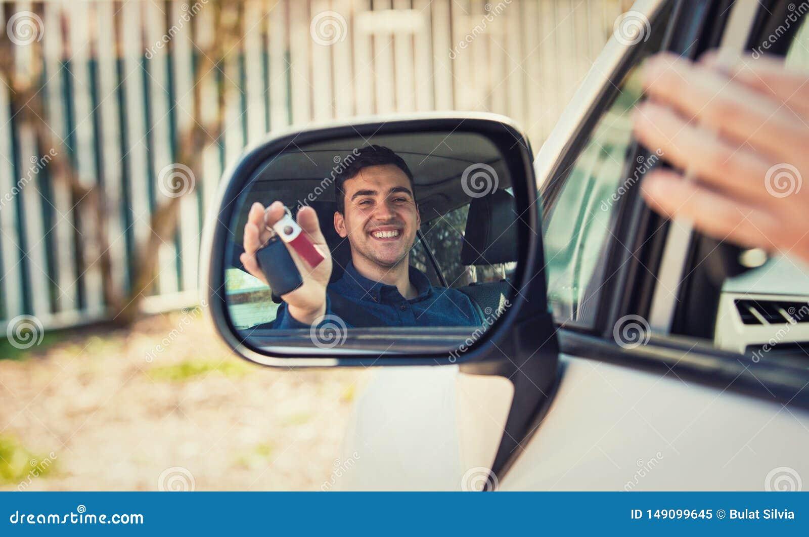 Zuf?llige Kerlfahrervertretungs-Autoschl?ssel in der Seitenansichtspiegelreflexion Erfolgreicher junger Mann kaufte einen Neuwage