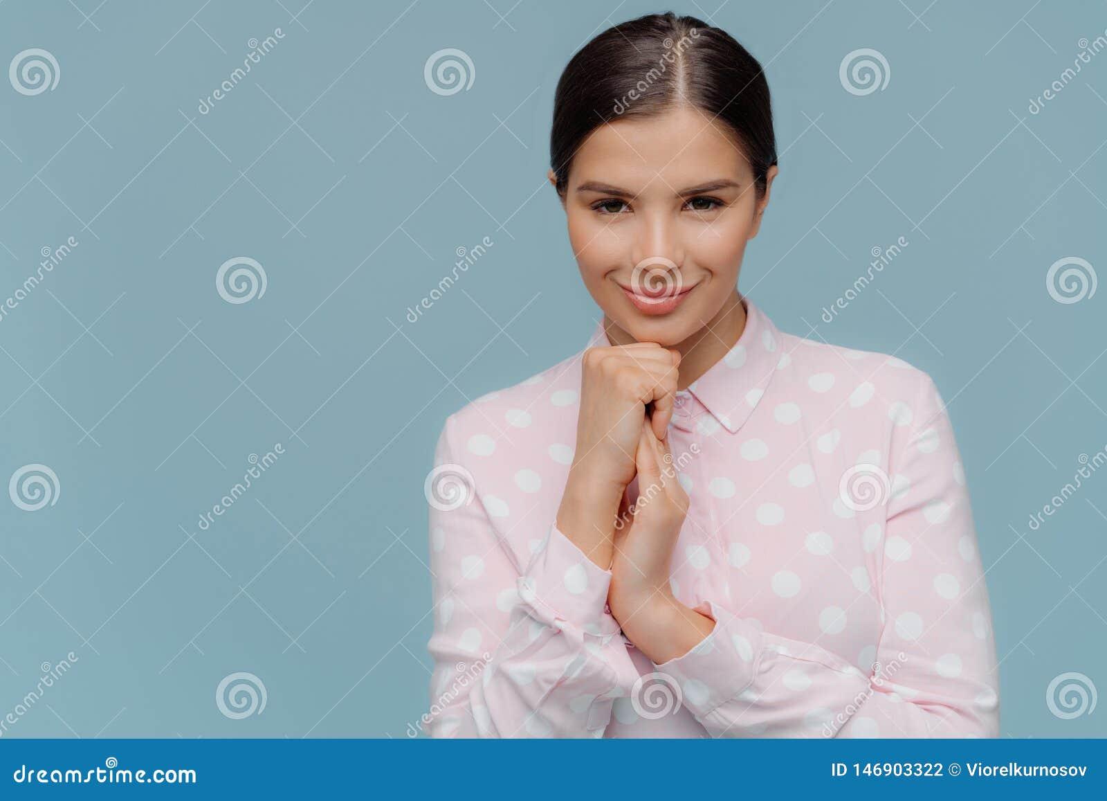 Zufriedene überzeugte reizende Frau mit Lächeln auf Gesicht, hält Hände nahe Kinn, betrachtet Kamera, hat dunkles gekämmtes Haar,