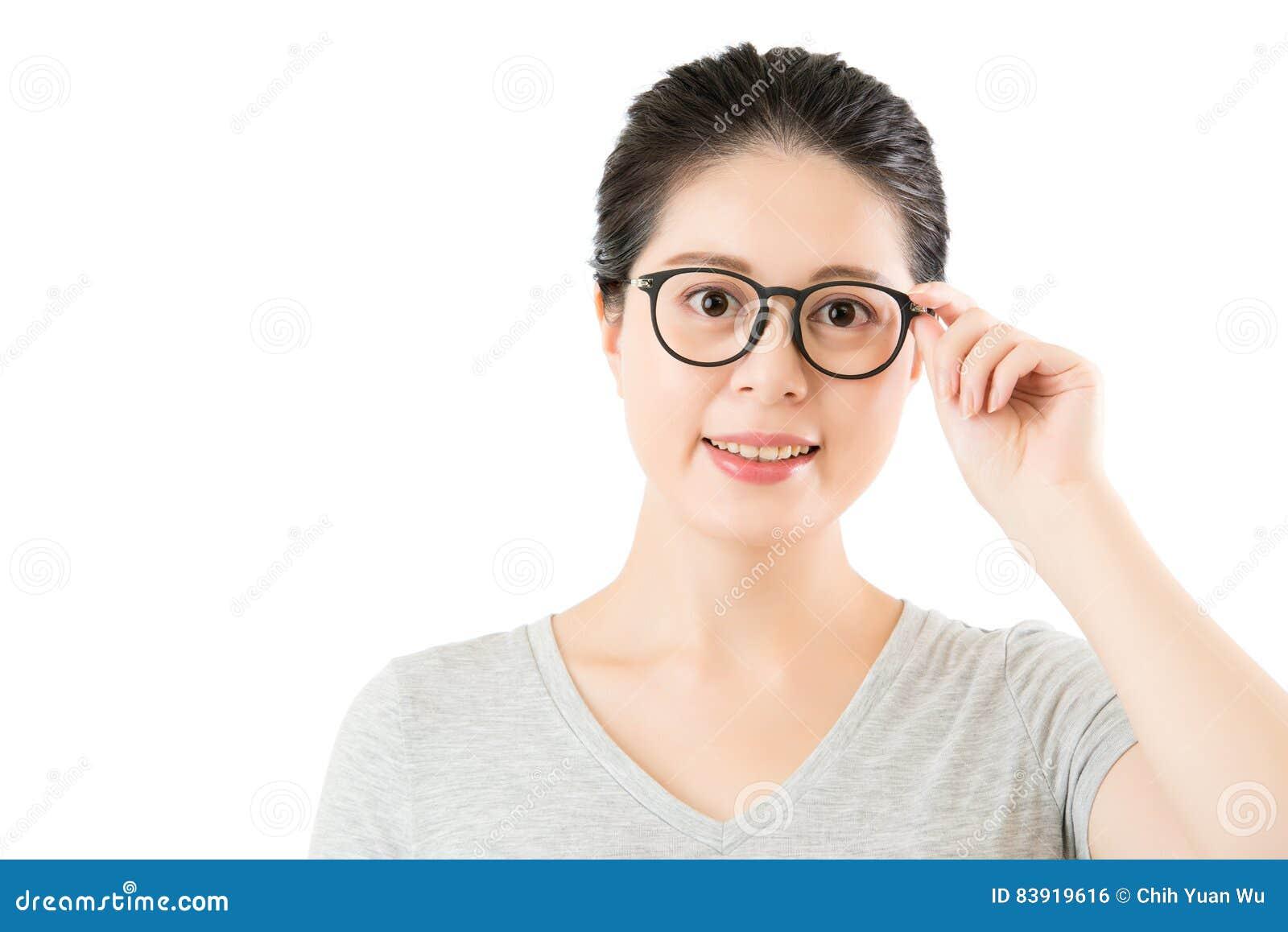 Zufriedenes natürliches Schauen der Asiatin über ihren noblen Gläsern