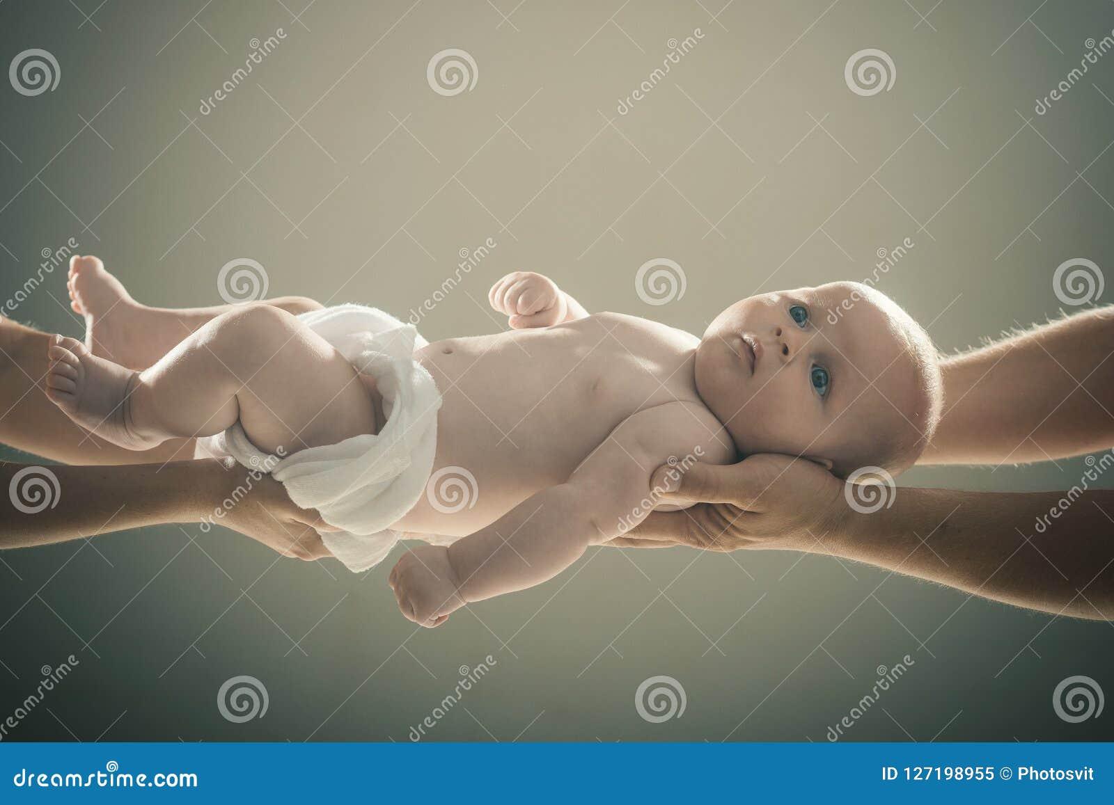 Zuigeling door handen van beide ouders op grijze achtergrond wordt gehouden die