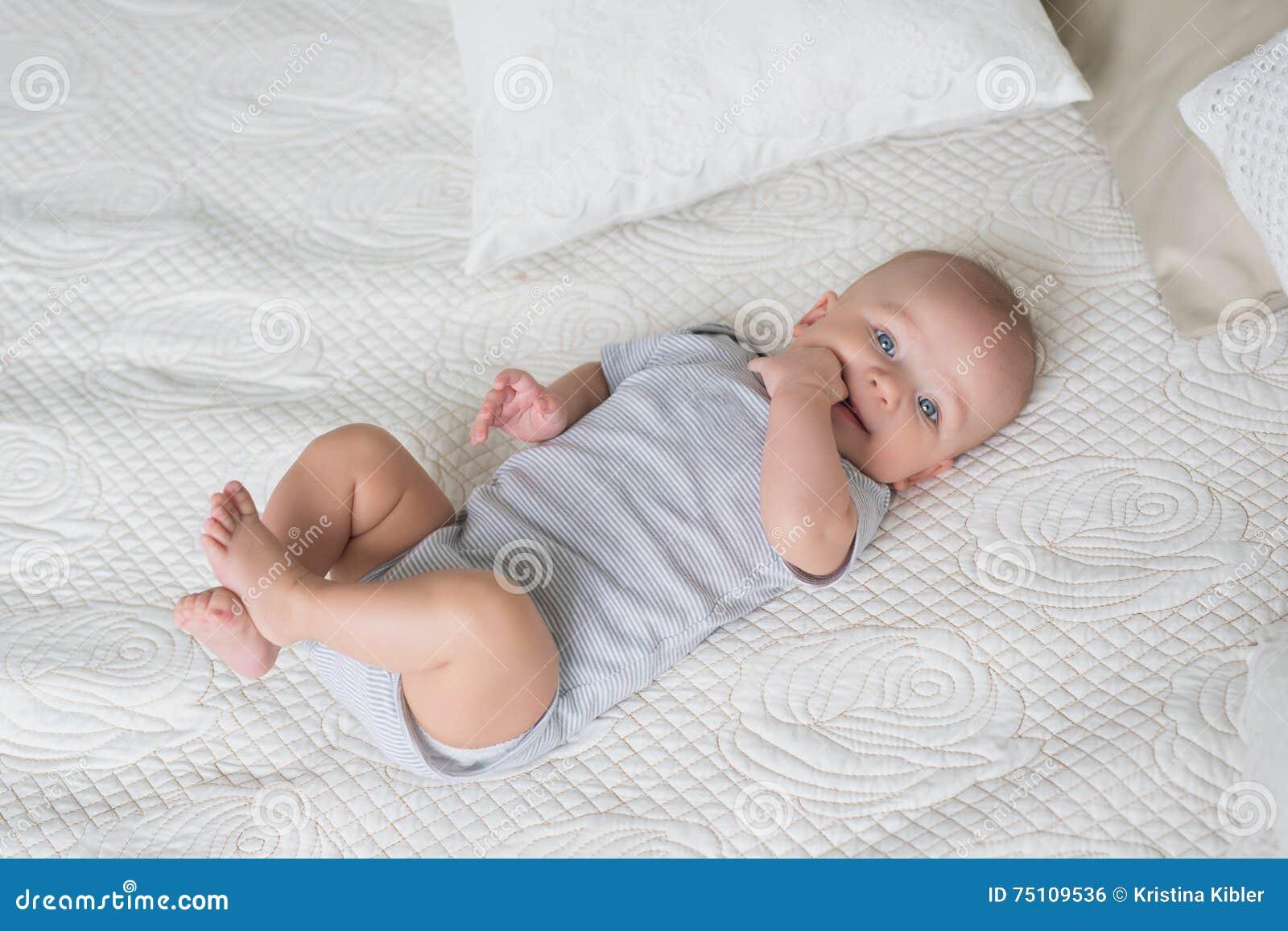Zuigeling in een grijze babykleren op een bed