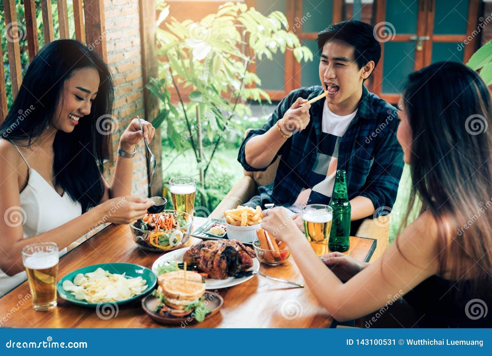 Zujubelndes Bier der asiatischen Leute an der glücklichen Stunde und am Lachen des Restaurants