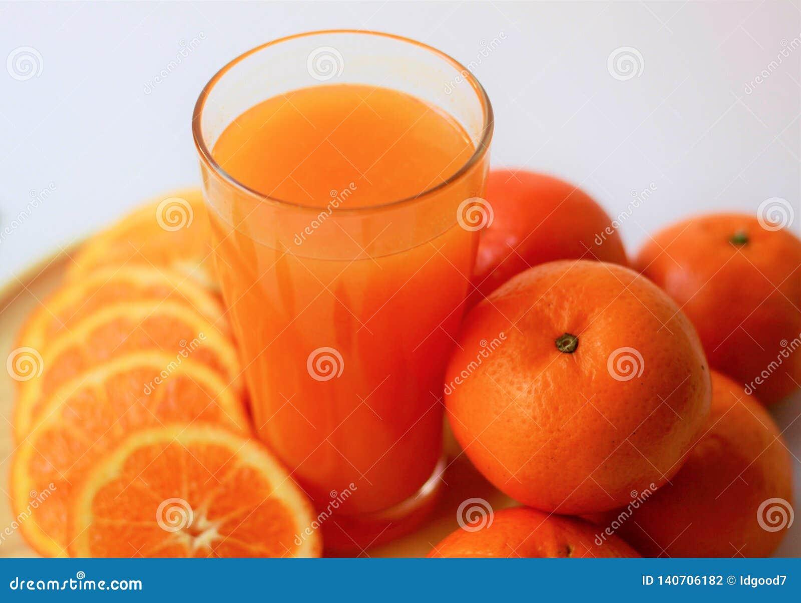 Zumo de naranja fresco del primer en vidrio, naranjas y rebanadas de naranjas, bebidas sanas, vitaminas frescas