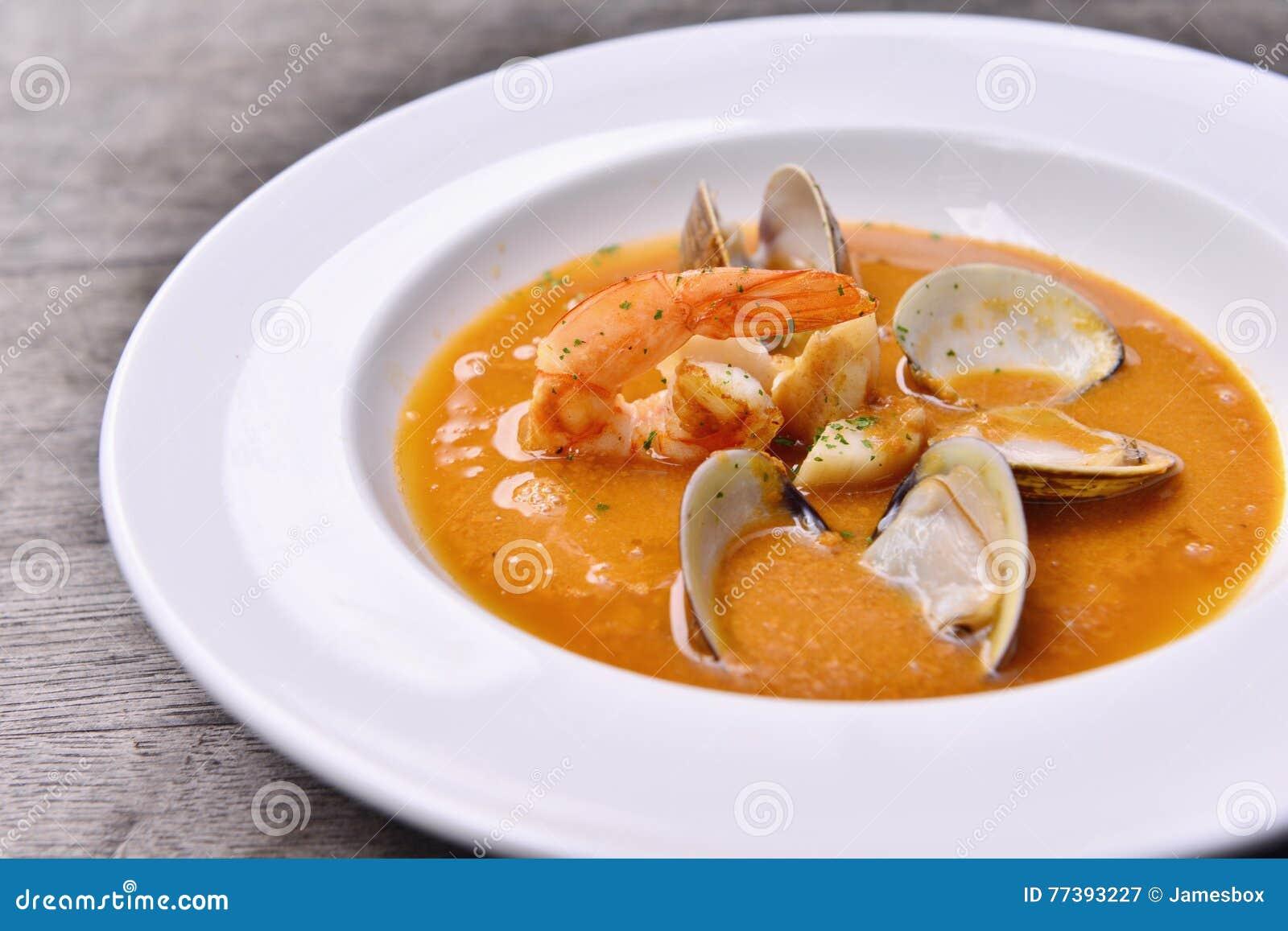 Zuppa di fungo selvaggia fresca con le vongole ed i gamberetti sul piatto bianco
