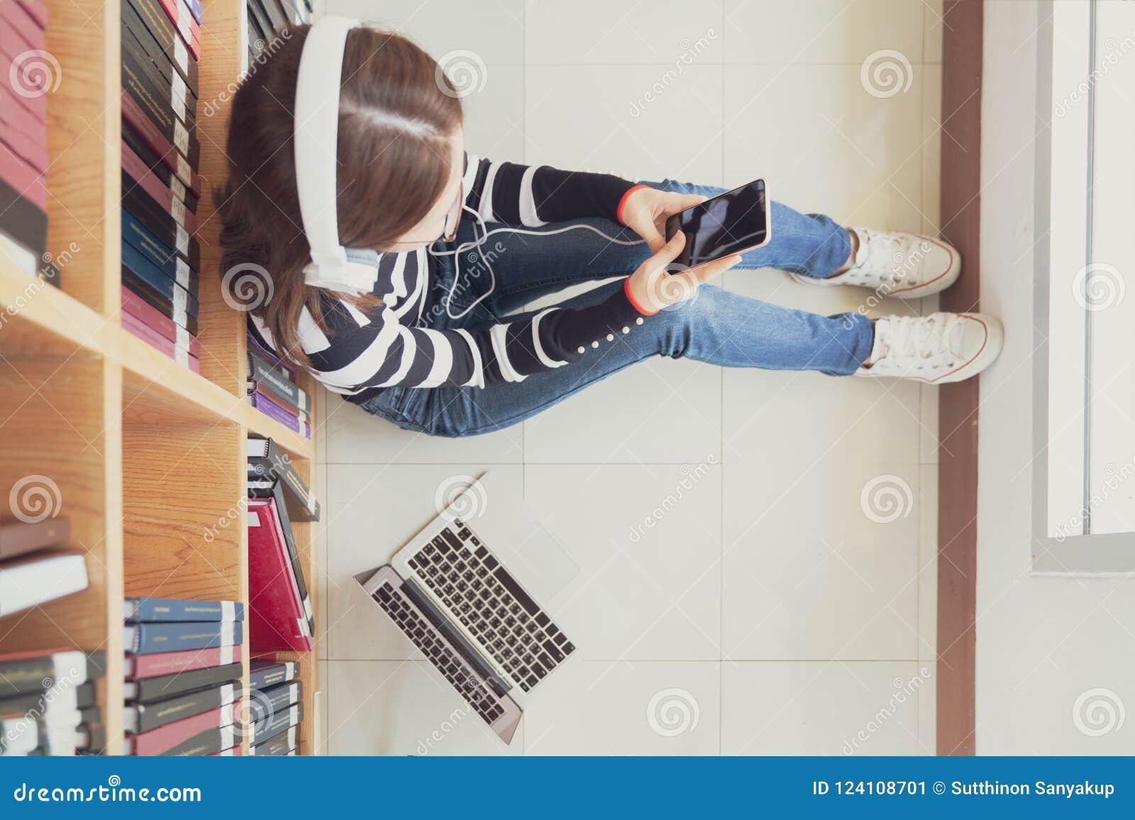 Zurück zu Schulbildungswissenscollege-Hochschulkonzept Studentinstudie in der Bibliothek unter Verwendung der Tablette und suchen