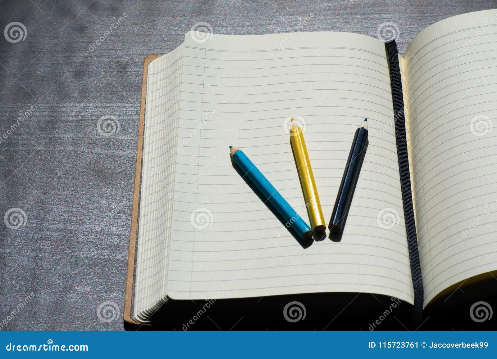 Zurück zu Schule-Noteblock-Zeichenstift-Bleistift-Farbblauem gelbem Notizbuch