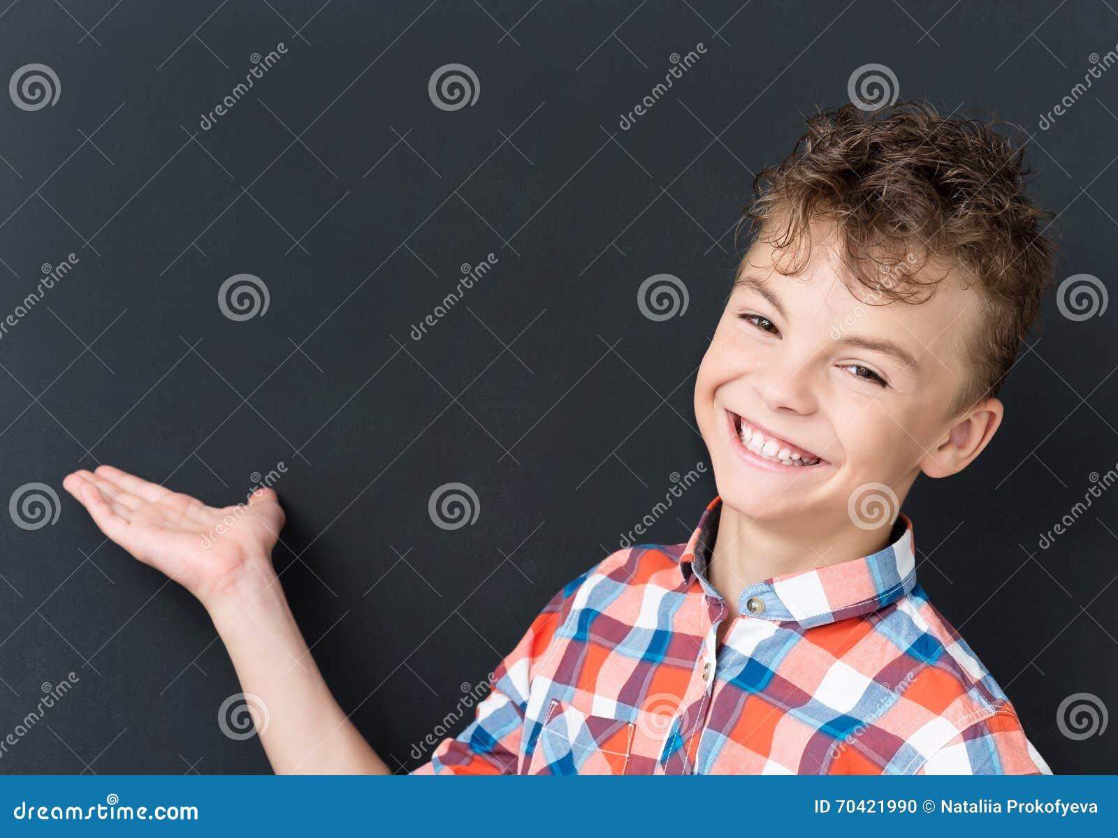 Zurück zu Schulkonzept - glücklicher Junge, der Kamera betrachtet