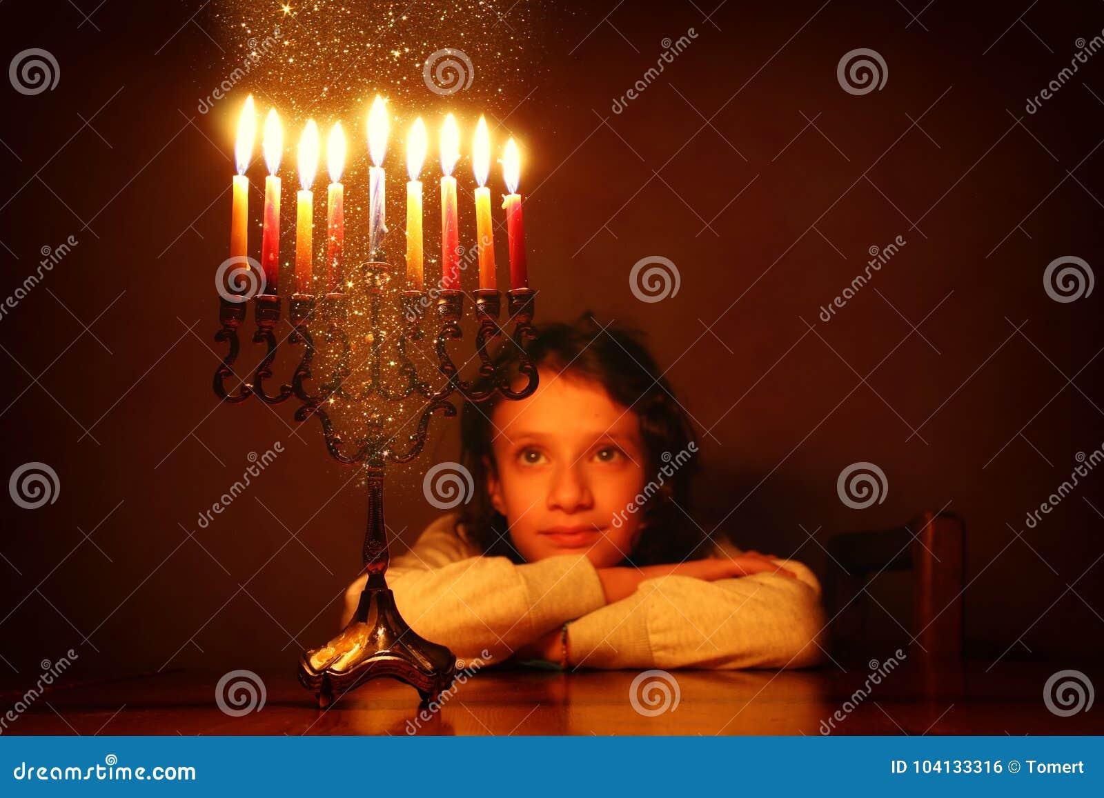 Zurückhaltendes Bild jüdischen Feiertag Chanukka-Hintergrundes mit dem netten Mädchen, das menorah u. x28 betrachtet; traditionel