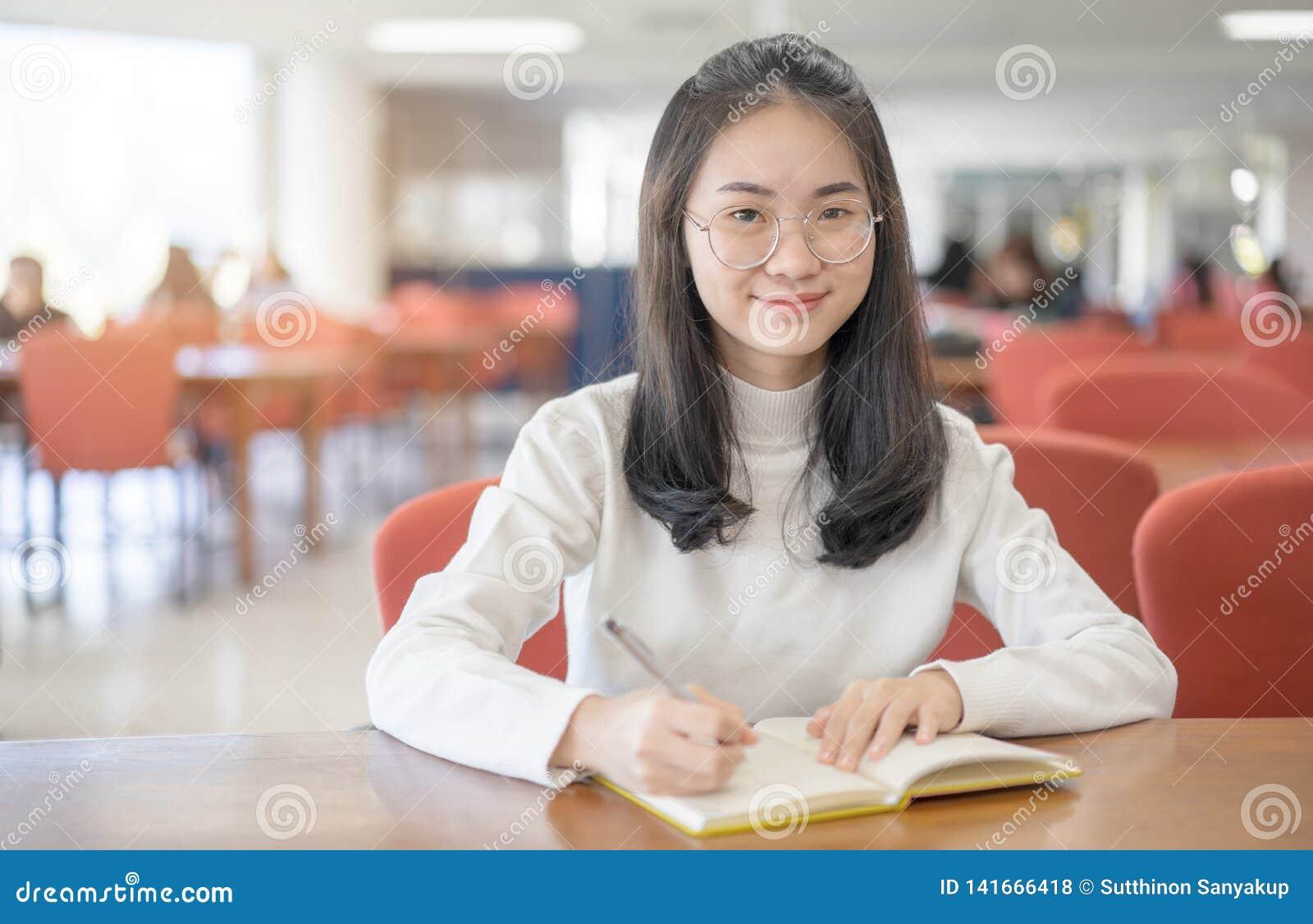 Zur?ck zu Schulbildungswissenscollege-Hochschulkonzept sch?ner weiblicher Student, der ihre B?cher gl?cklich l?cheln h?lt