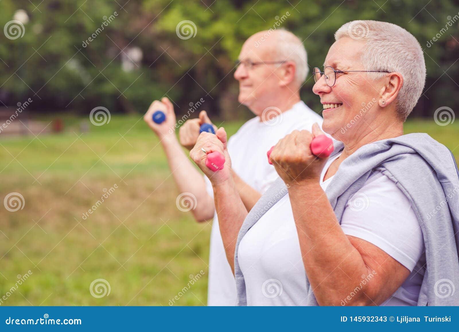 Zusammen verbessern wir Training - lächelnde ältere Paarpraxis mit Dummköpfen