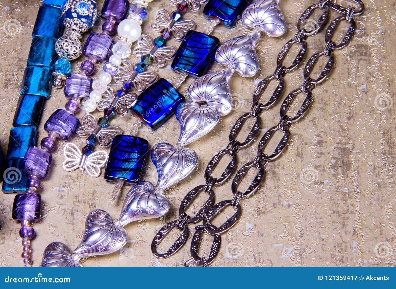 Zusammengebaute Perlen und Ketten in der kurzen Armbandlänge auf goldenem Hintergrund