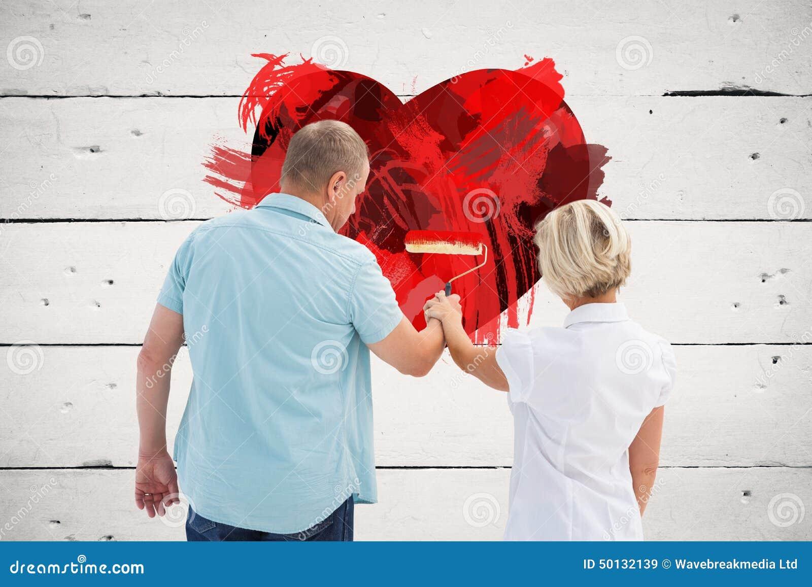 Zusammengesetztes Bild der malenden weißen Wand der glücklichen älteren Paare