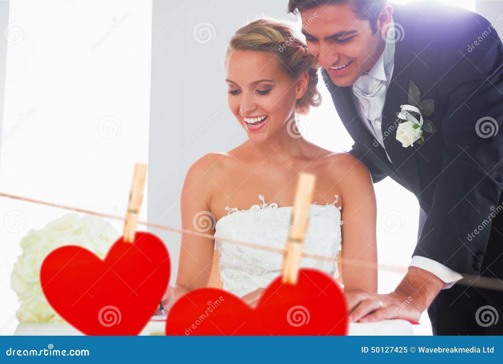 Zusammengesetztes Bild der unterzeichnenden Hochzeit der glücklichen jungen Paare registrieren