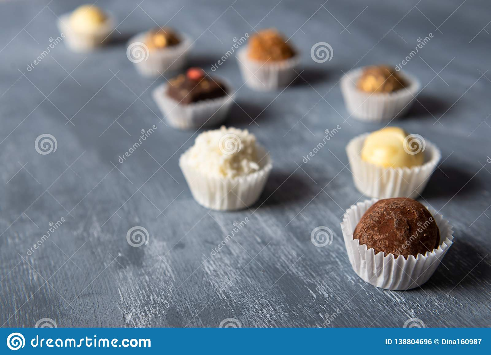 Zusammenstellung von feinen Pralinen, von Weiß, von Dunkelheit und von Milchschokolade auf grauem Hintergrund Bonbons Hintergrund