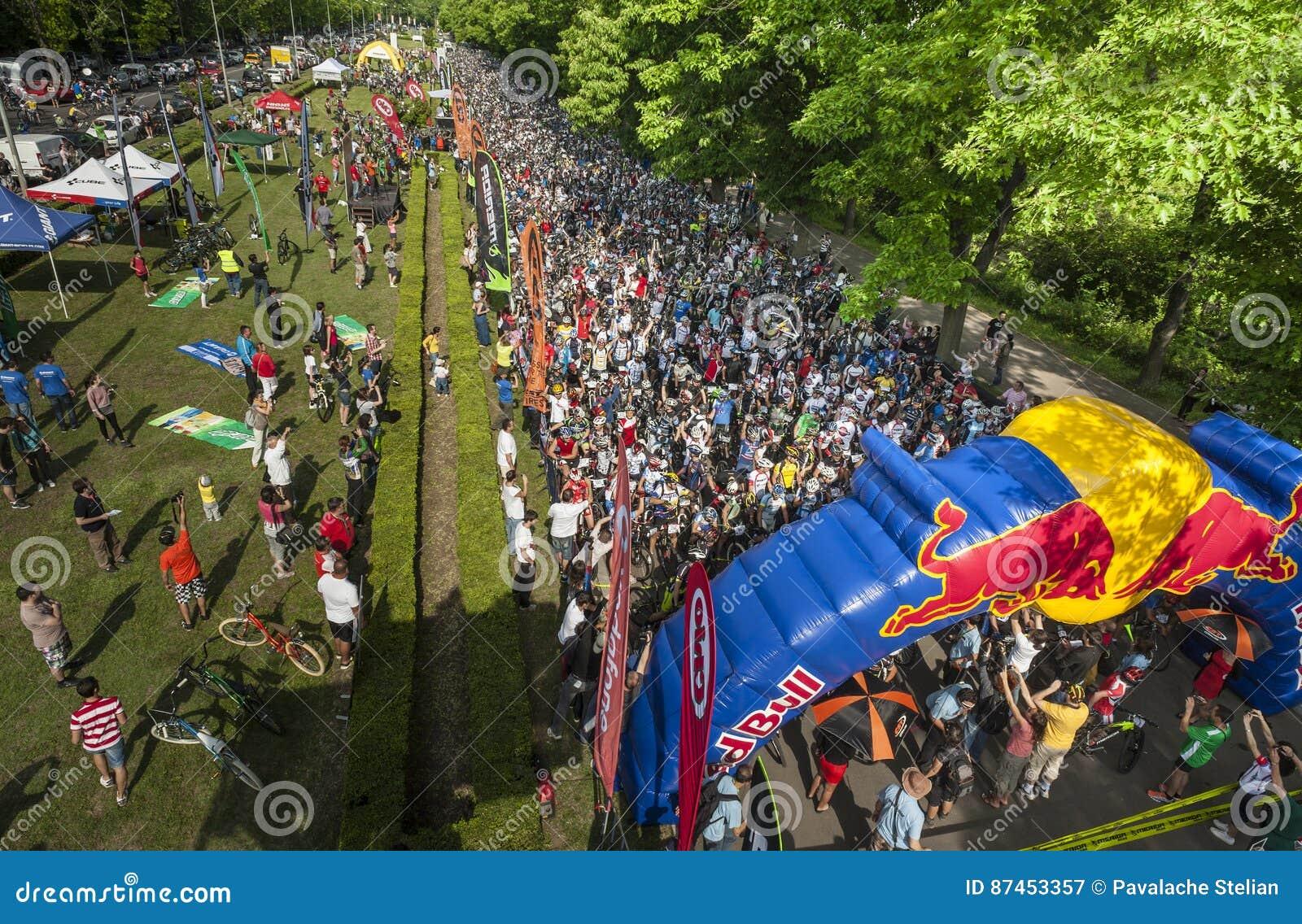 Zuschauer gegen die gedrängten Athleten bereit, in einem mountainbike Wettbewerb zu beginnen