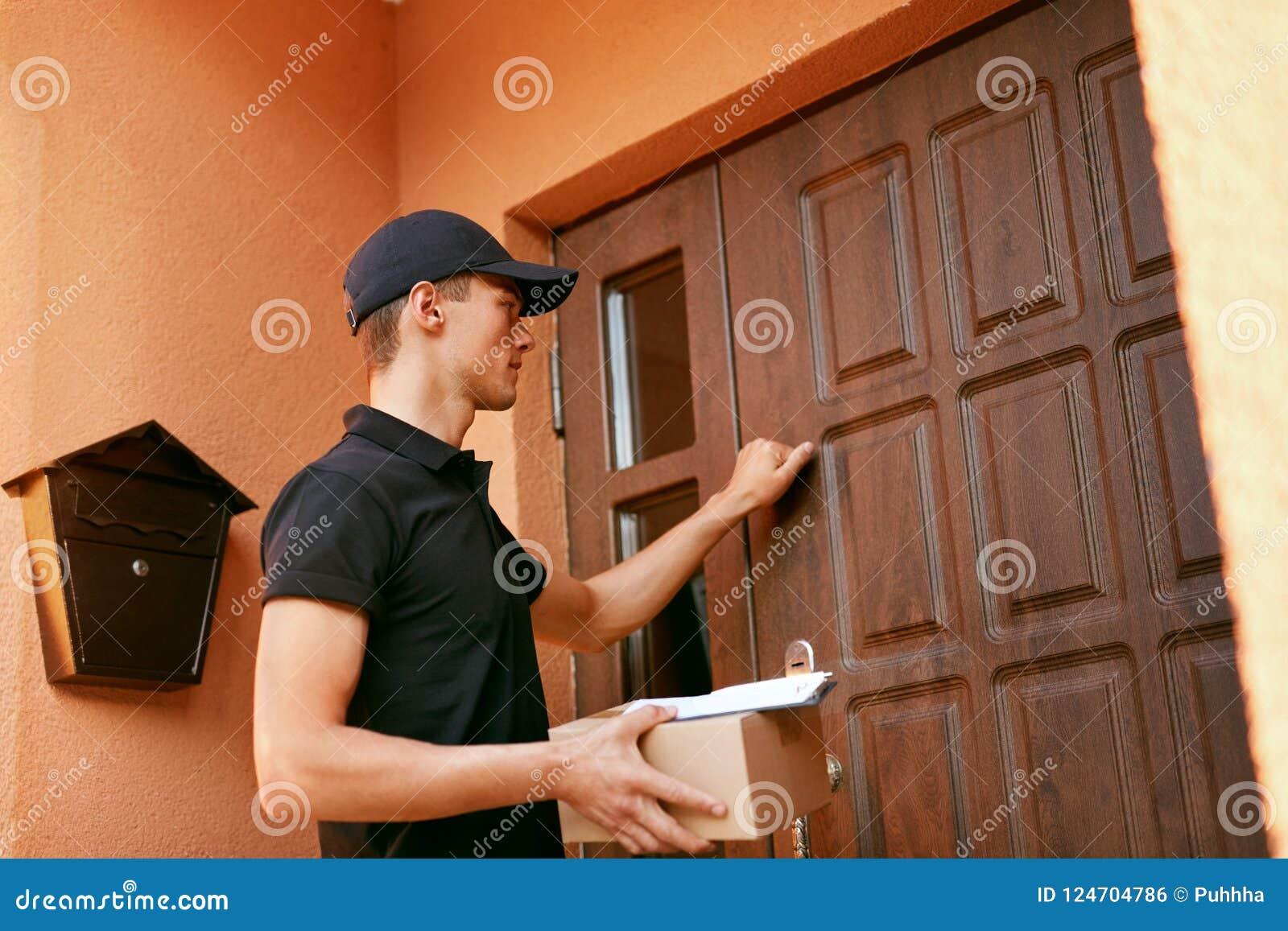 Zustelldienst Stattliche Arbeitskraft mit einem Kasten Kurier-With Package Near-Kunden-Tür