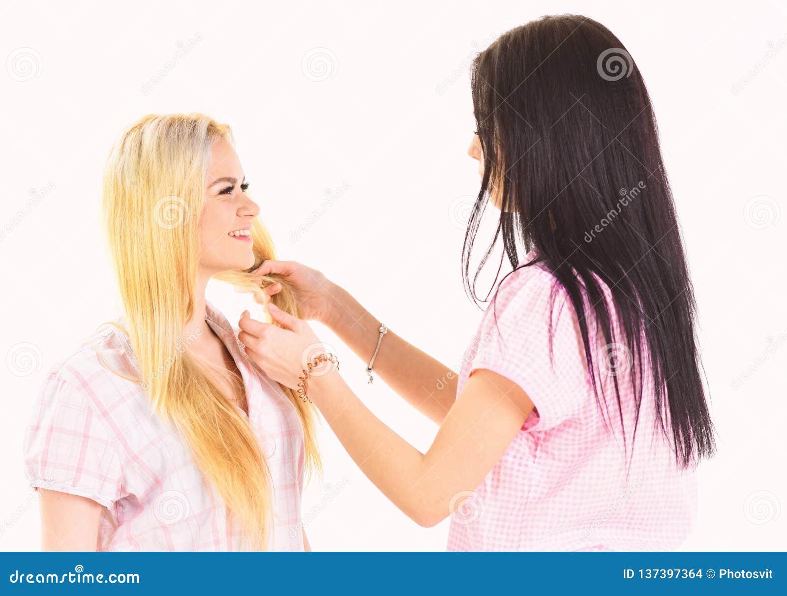 Zusters, beste vrienden die in pyjama s vlecht, kapsel maken elkaar Blonde, brunette op het glimlachen gezichten in kleren voor s
