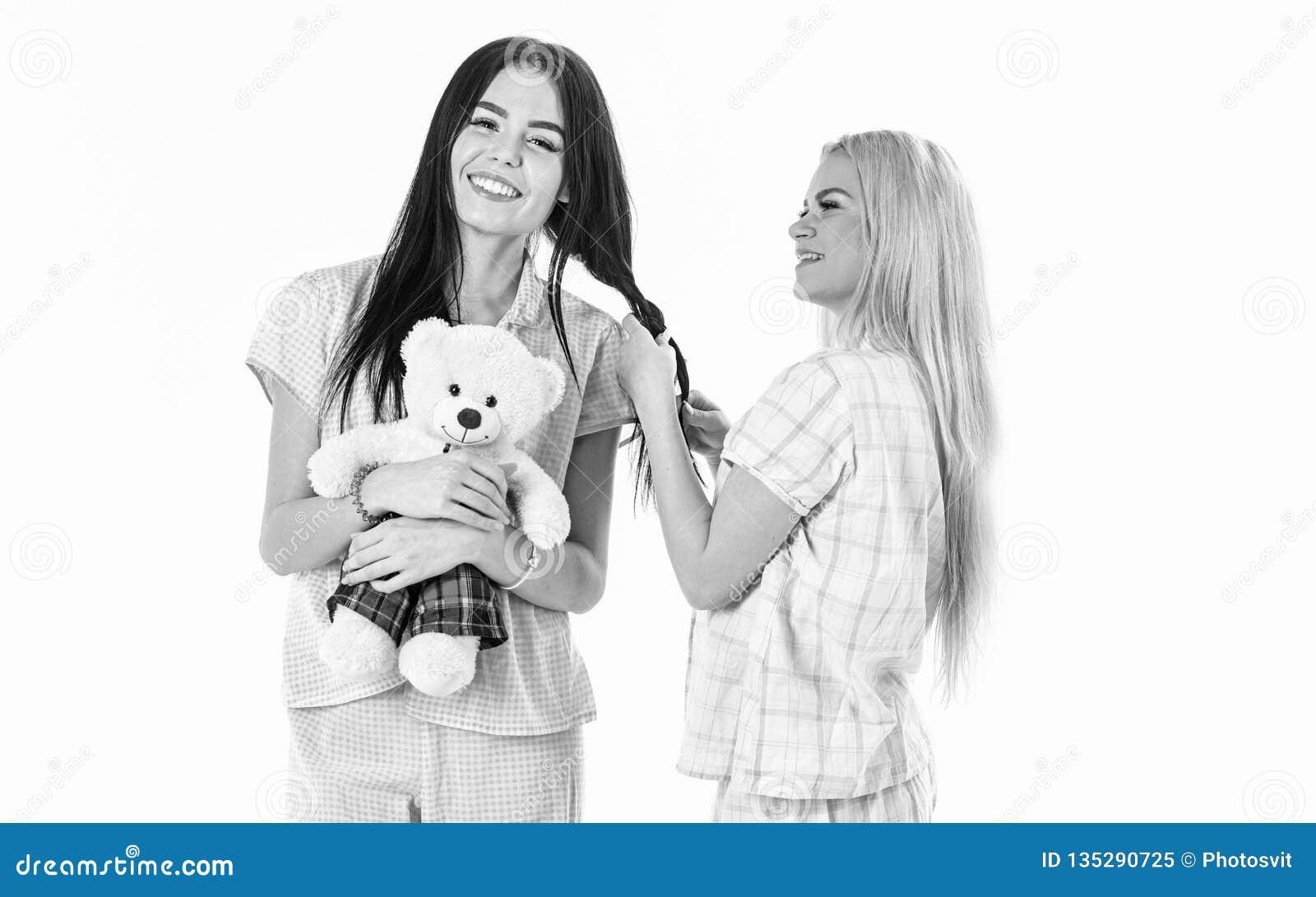 Zusters, beste vrienden die in pyjama s vlecht, kapsel maken elkaar Meisjes in roze pyjama s, geïsoleerde witte achtergrond