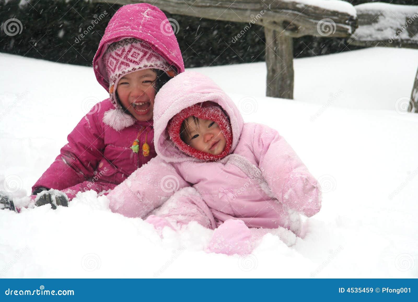 Zusters die in de sneeuw spelen