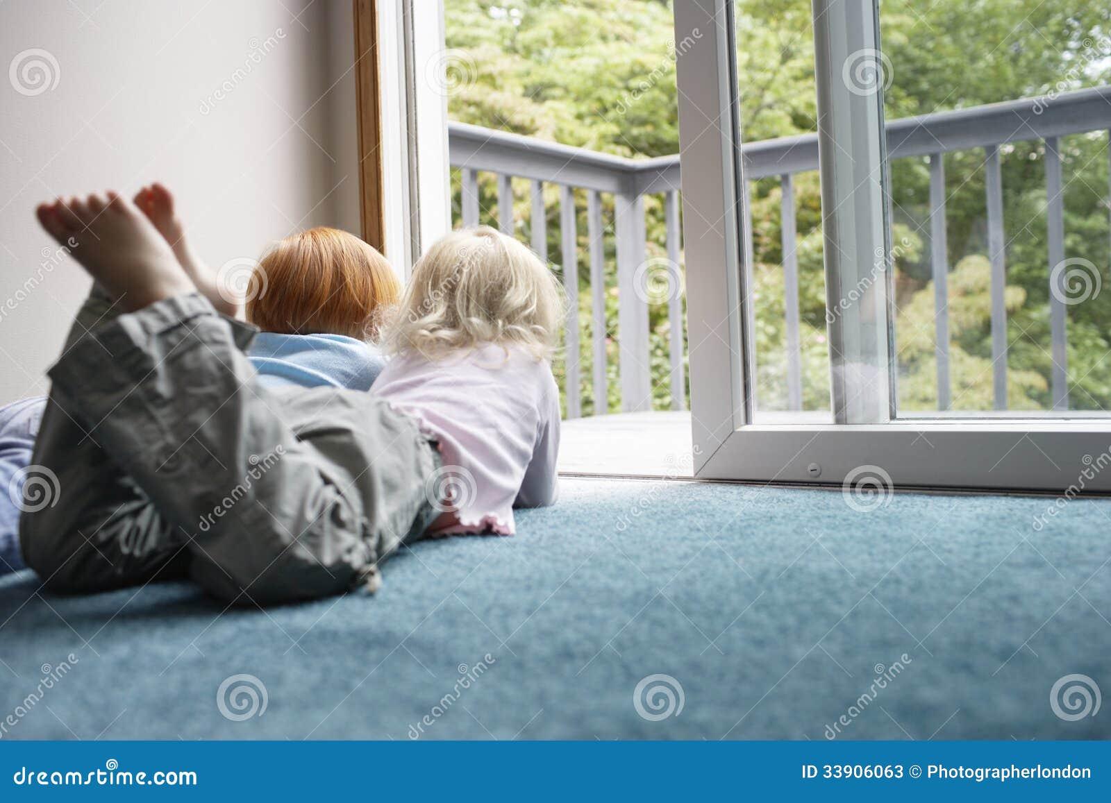Tapijt Voor Balkon : Zusters die door balkon kijken terwijl het liggen op tapijt stock