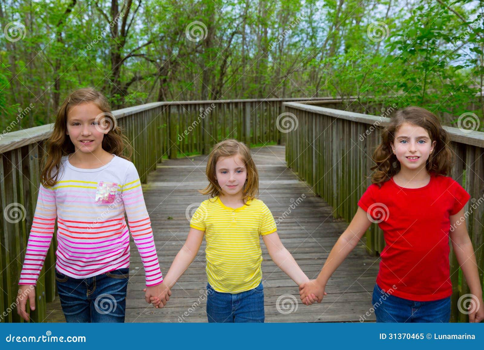 Zustervrienden die holdingshanden op meerhout lopen