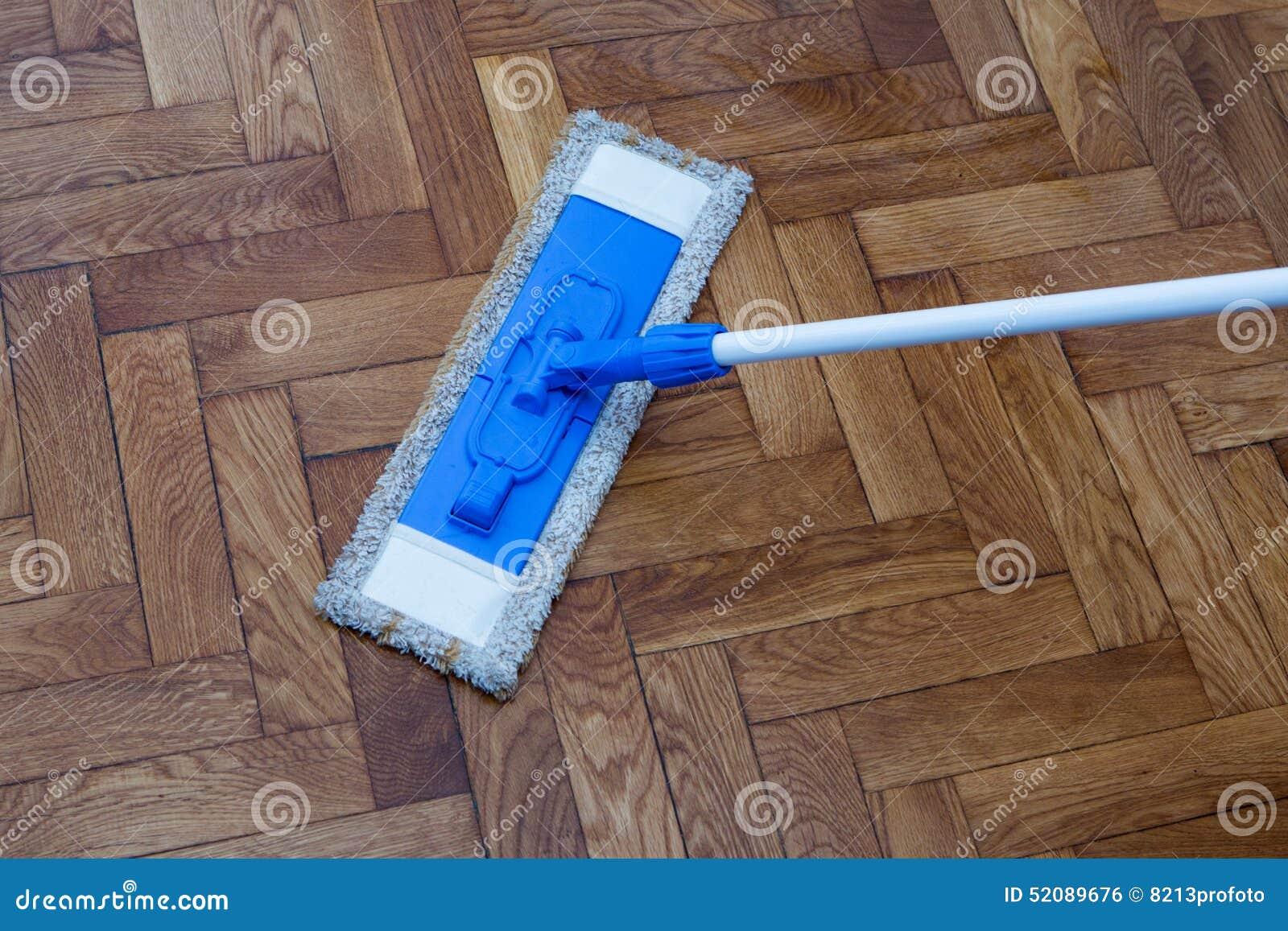 Houten Vloer Onderhoud : Zwabber die een houten vloer schoonmaken stock foto afbeelding