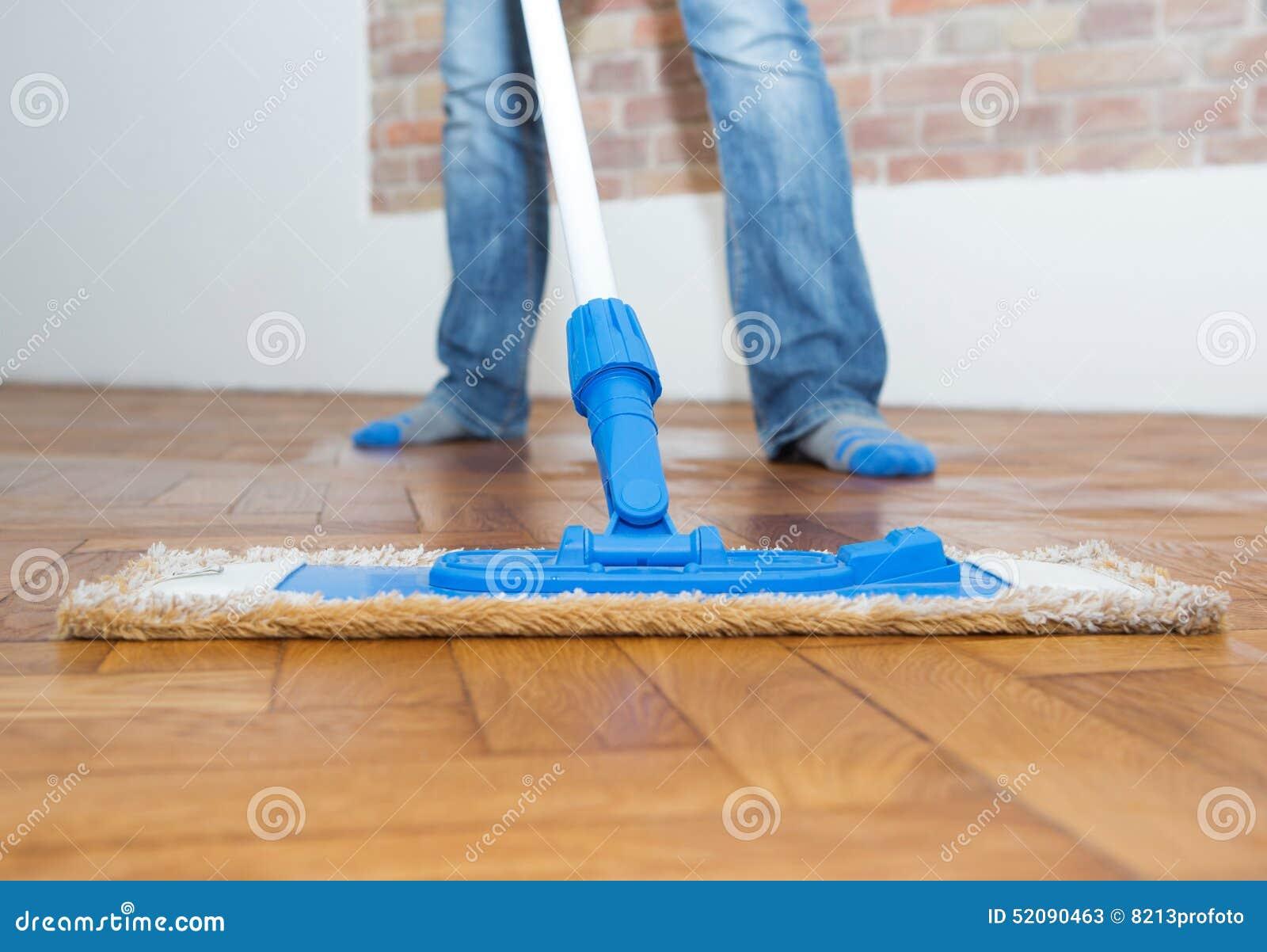 Zwabber die een houten vloer schoonmaken stock afbeelding