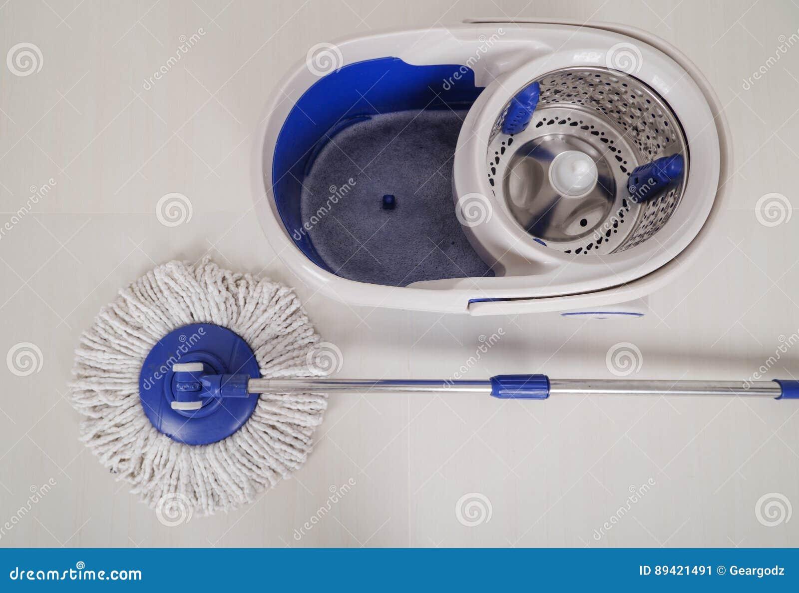 Zwabber en blauwe emmer voor het schoonmaken van vloer stock