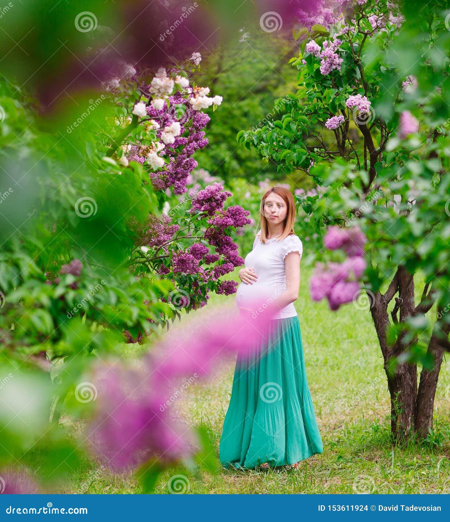 Zwanger meisje in het de zomerpark in openlucht