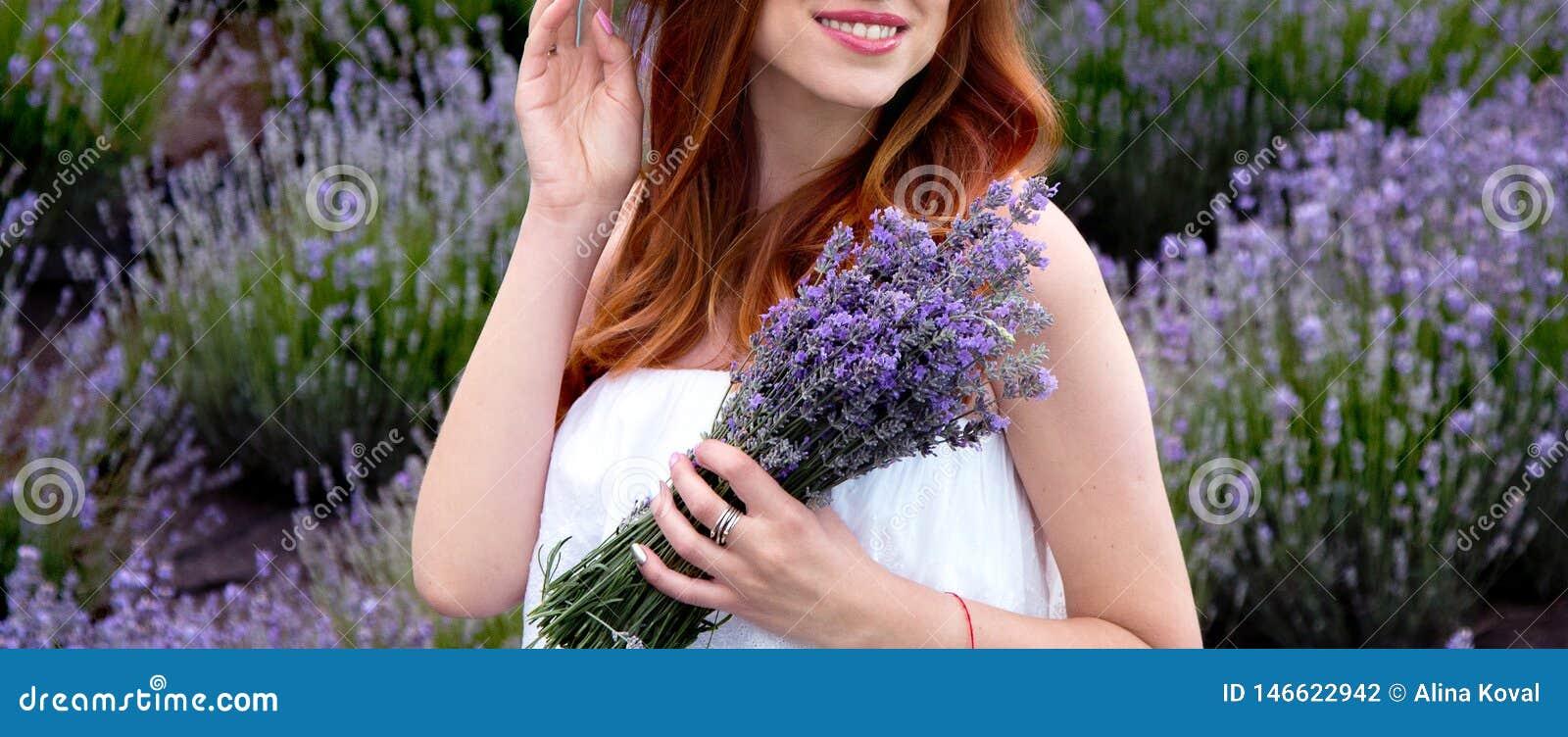 Zwanger meisje in lavendel in de de zomertuin