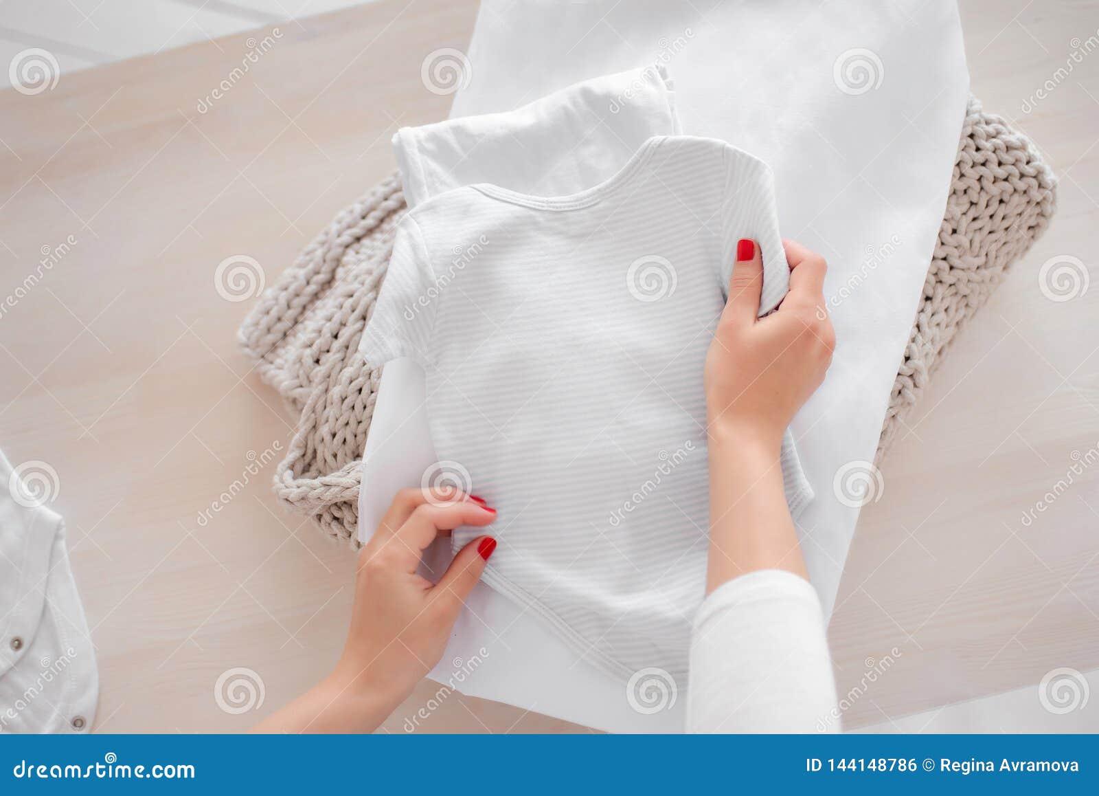 Zwangere de babykleren van meisjesvouwen in een stapel De verantwoordelijkheden van vrouwen thuis Het vouwen van kleren