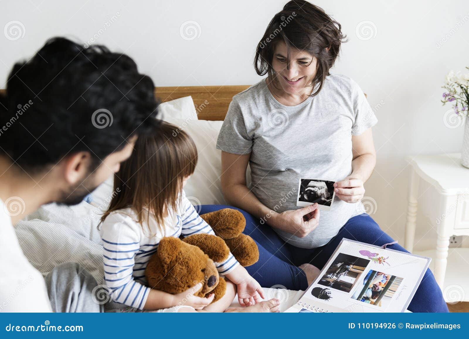 Zwangere familie die door een album van de familiefoto kijken
