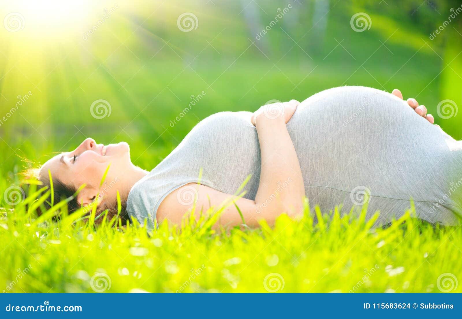 Zwangere midden oude vrouw wat betreft haar buik die op groen gras liggen, die van aard genieten Geïsoleerd op Wit