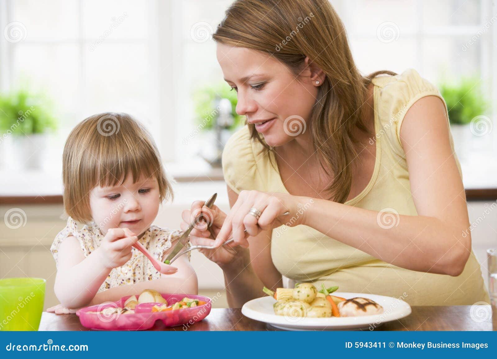 Zwangere moeder die in keuken kip eet en vege