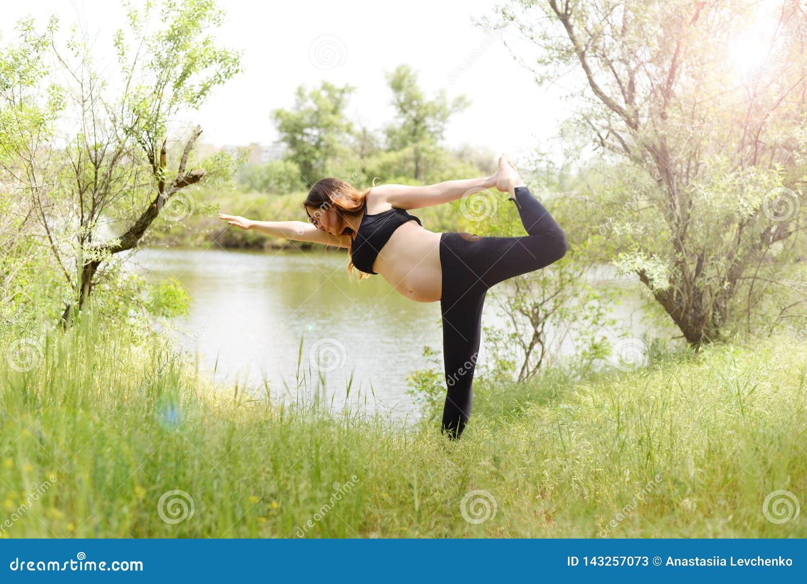 Zwangere mooie vrouwenyoga in openlucht op het gras in zonnige de zomerdag
