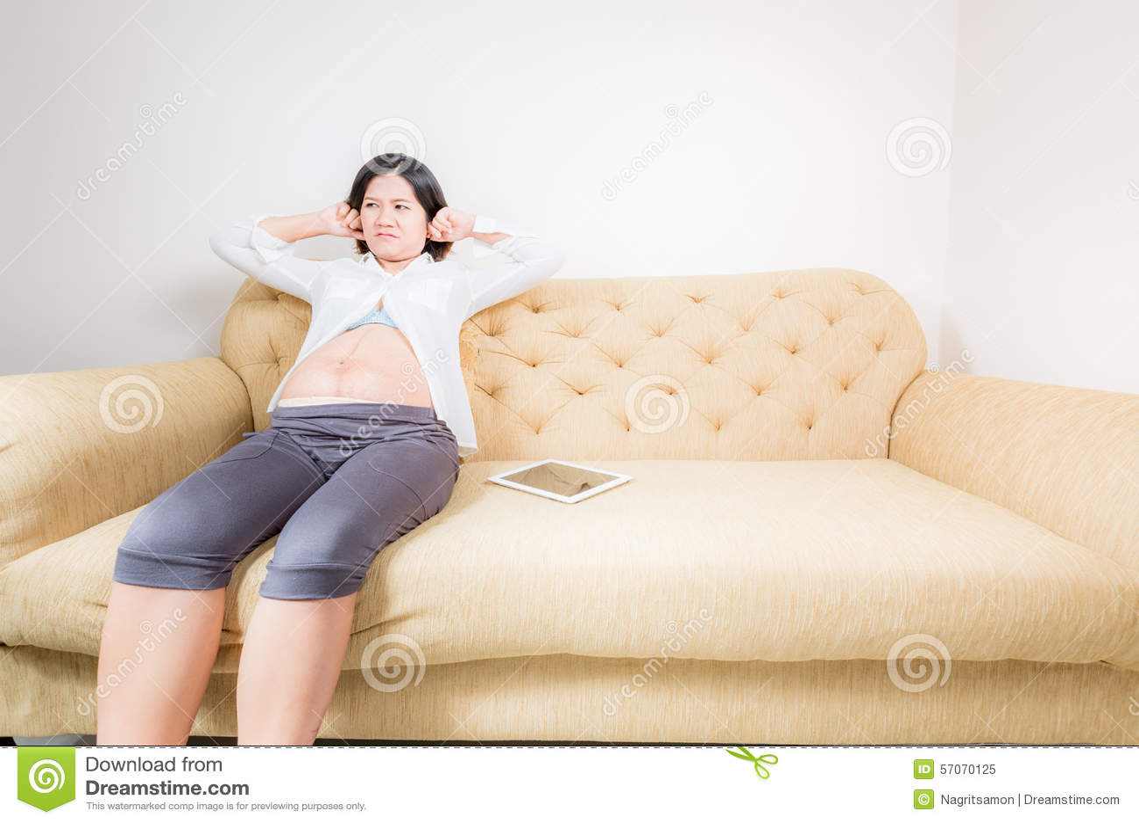 Zwangere vrouw die ernstig zittend op laag kijken